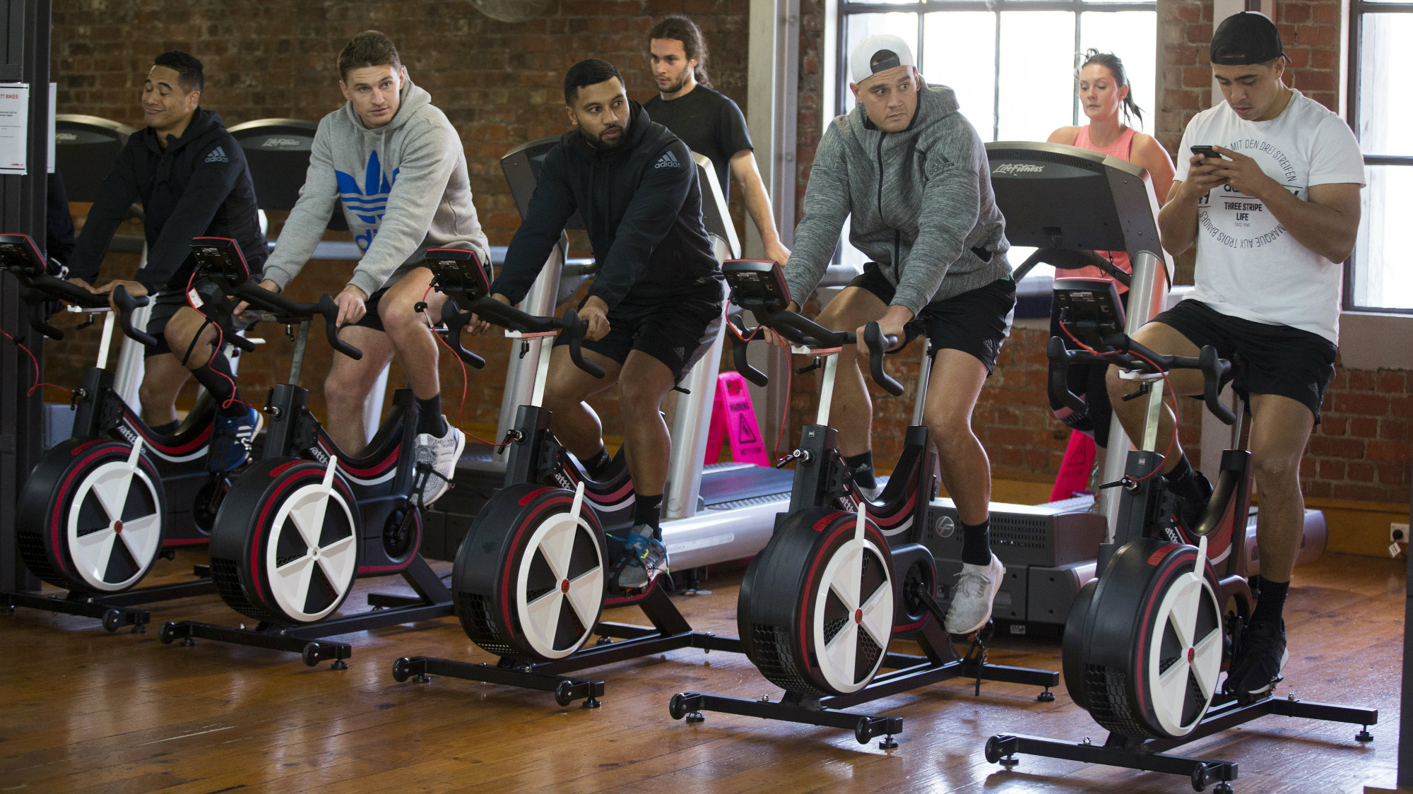 People work out on stationary bikes and treadmills at a gym