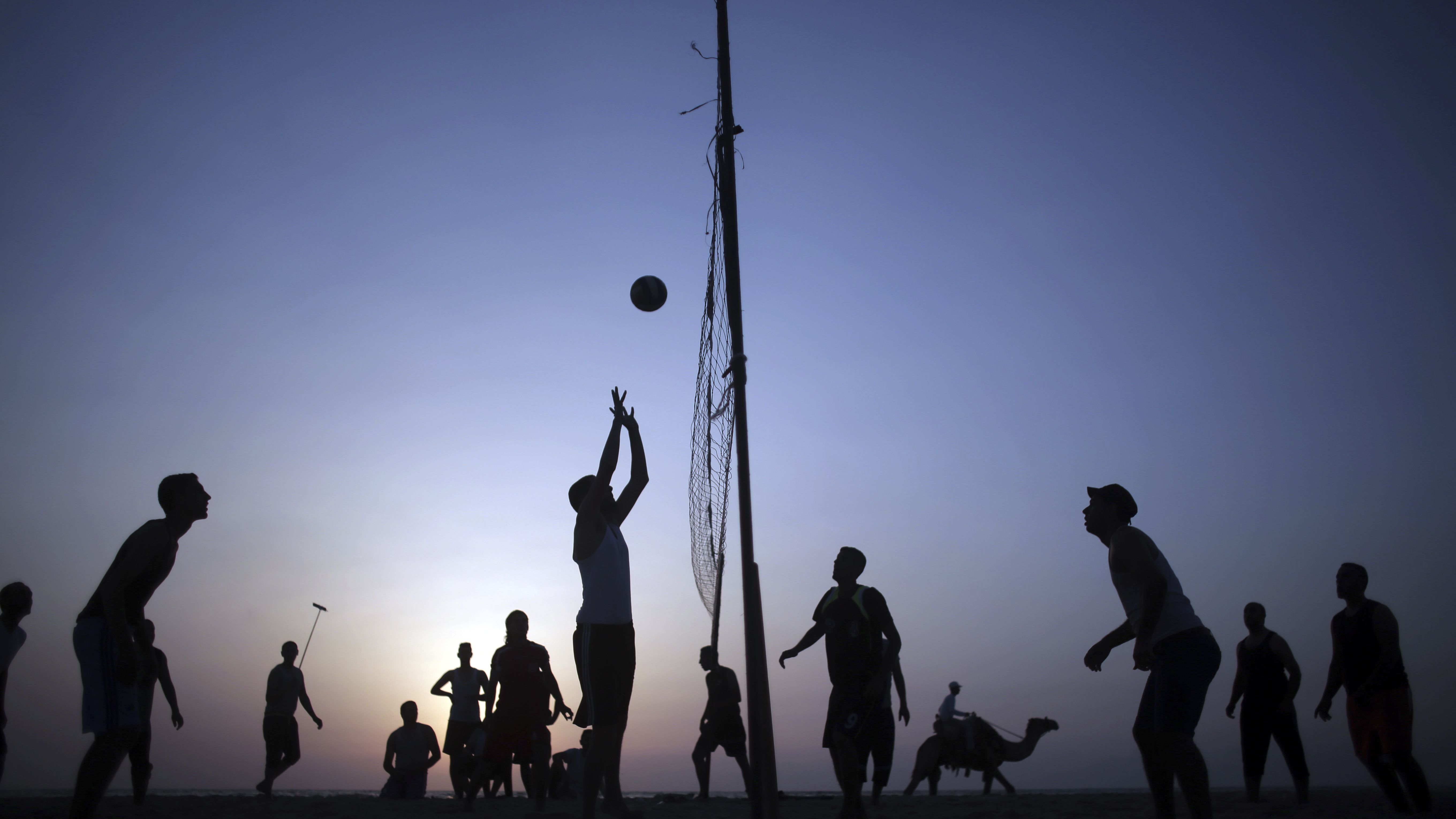 Palestinians play volleyball on the beach as the sun sets over Gaza City, Thursday, July, 13, 2017.