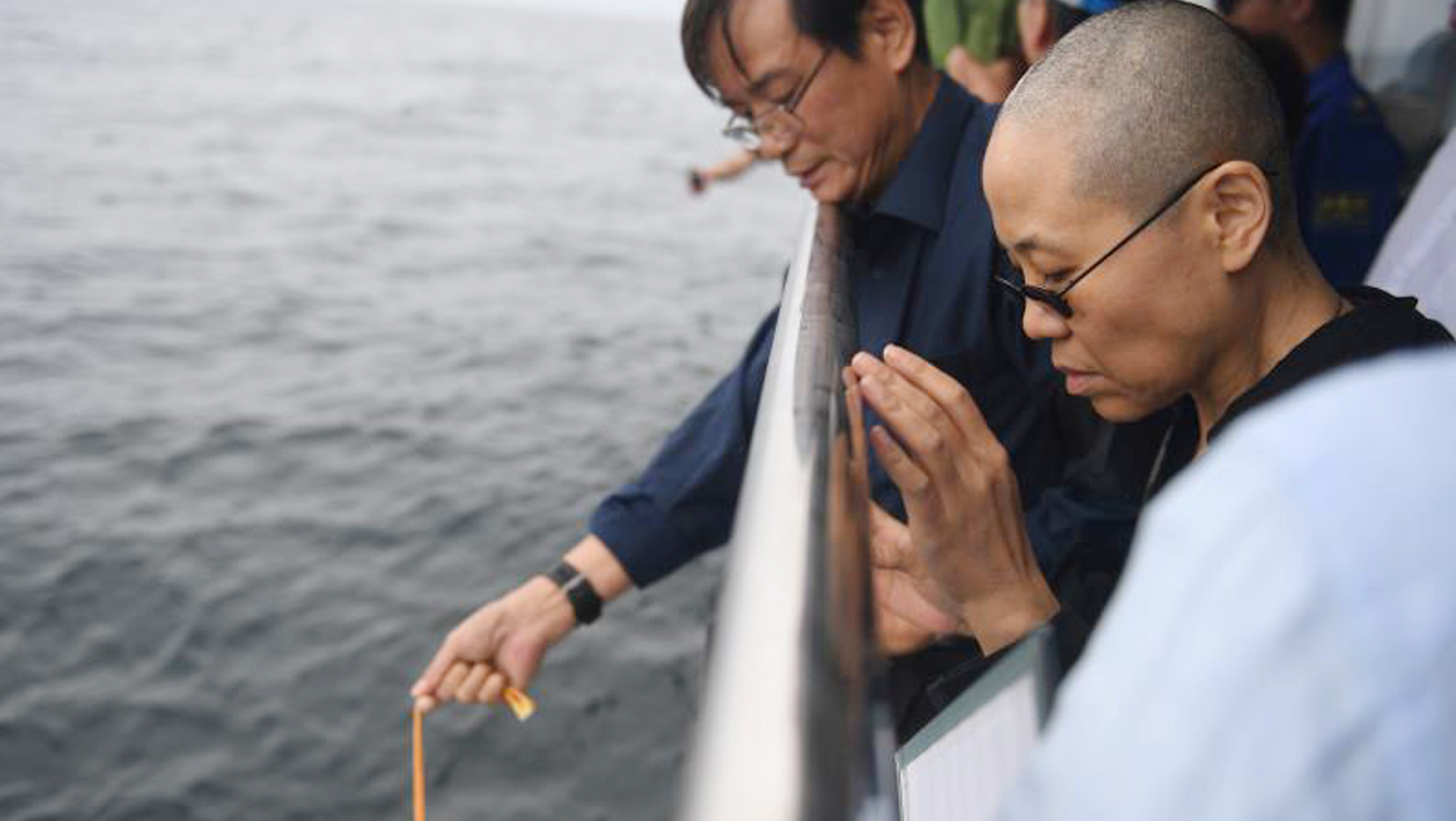 Liu Xia, the wife of Chinese Nobel Peace laureate Liu Xiaobo, watches as Liu's ashes are lowered into the water.