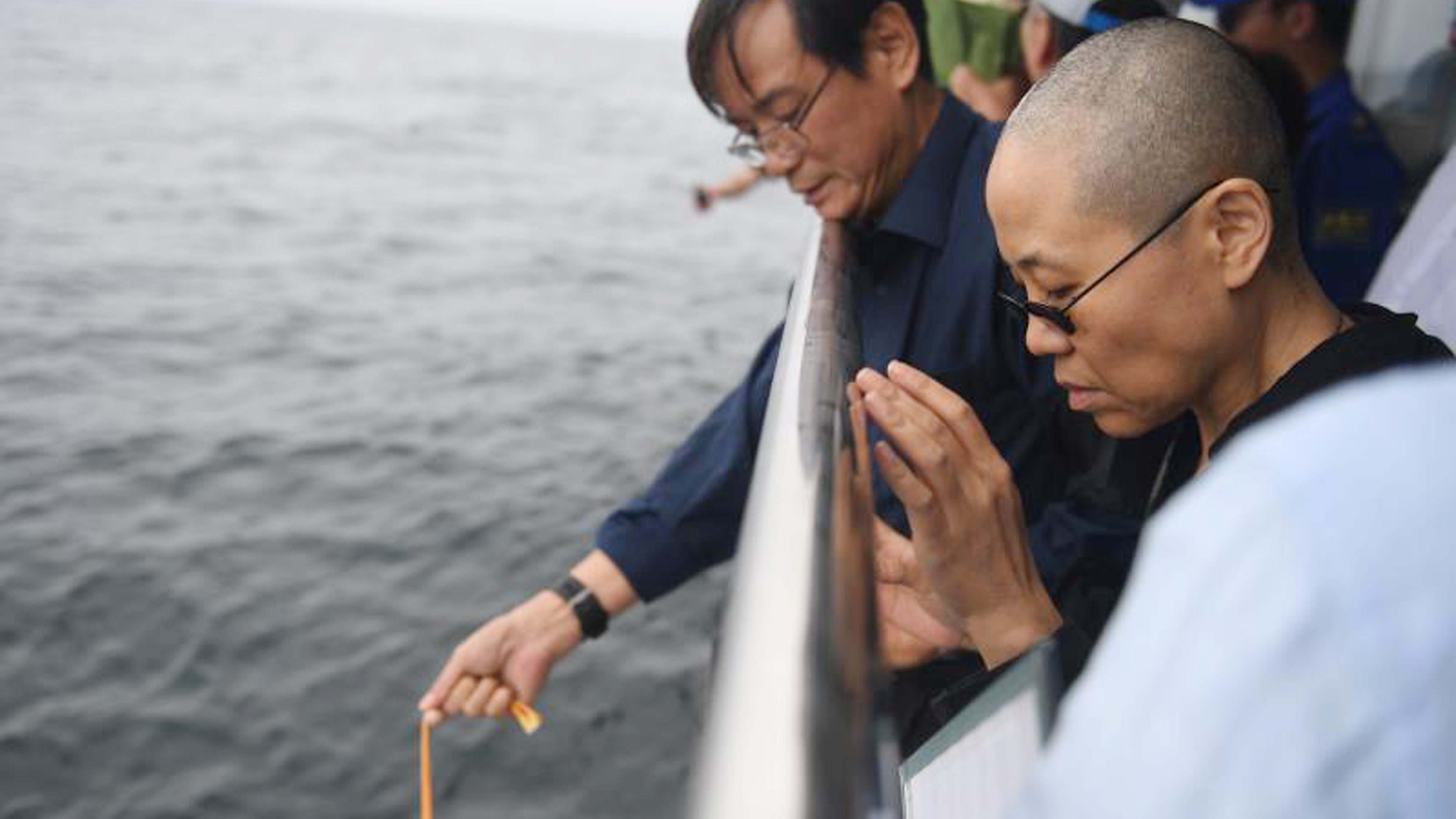 In this photo provided by the Shenyang Municipal Information Office, Liu Xia, the wife of imprisoned Chinese Nobel Peace Prize laureate Liu Xiaobo, watches as Liu's ashes are buried at sea off the coast of Dalian in northeastern China's Liaoning Province, Saturday, July 15, 2017. China cremated the body of Liu on Saturday, July 15, 2017, who died this week after a battle with liver cancer amid international criticism of Beijing for not letting him travel abroad as he had wished.