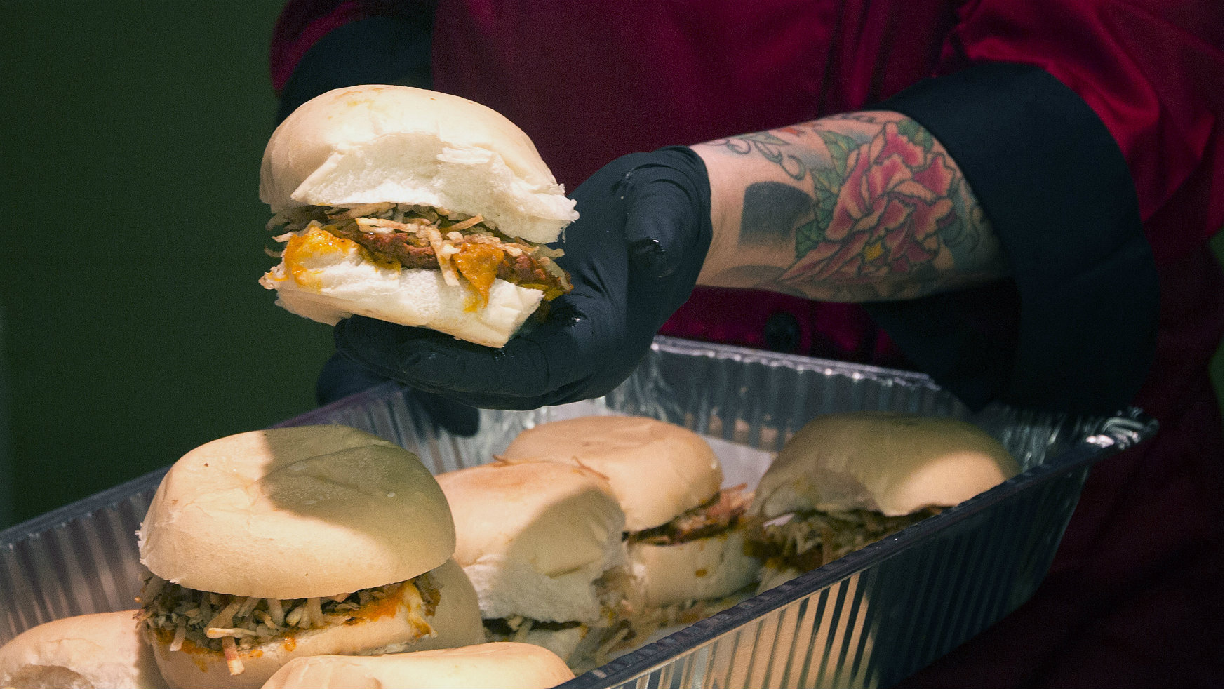 Hamburger served by someone with tatoos
