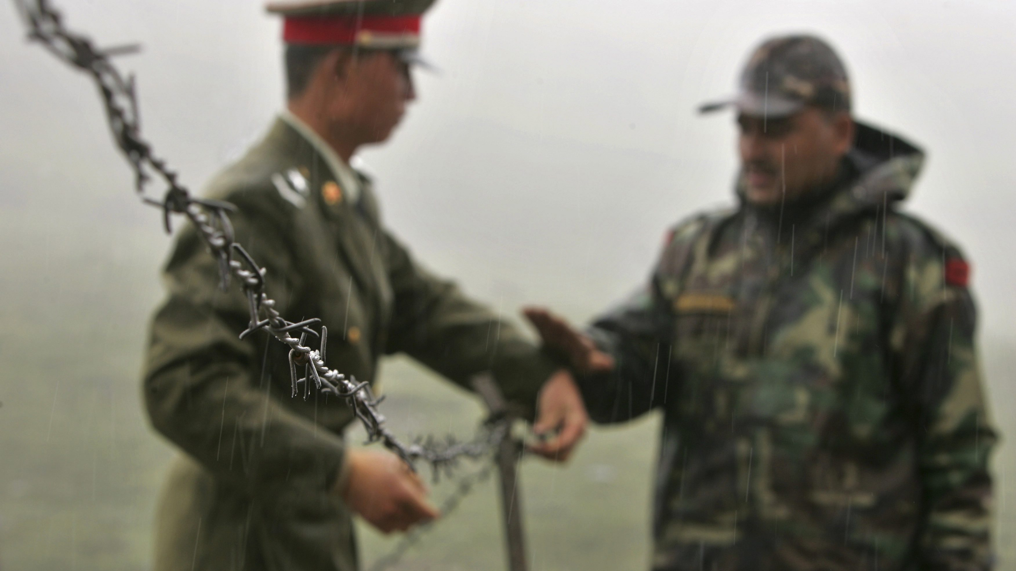 FILE - In this July 5, 2006 file photo, a Chinese soldier, left, and an Indian soldier put into place a barbed wire fence removed temporarily for Chinese officials to cross back to their country after a meeting with their Indian counterparts at the international border at Nathula Pass, in northeastern Indian state of Sikkim. While the recent troop standoff in a remote Himalayan desert spotlights a long-running border dispute between China and India, the two emerging giants are engaged in a rivalry for global influence that spreads much farther afield.