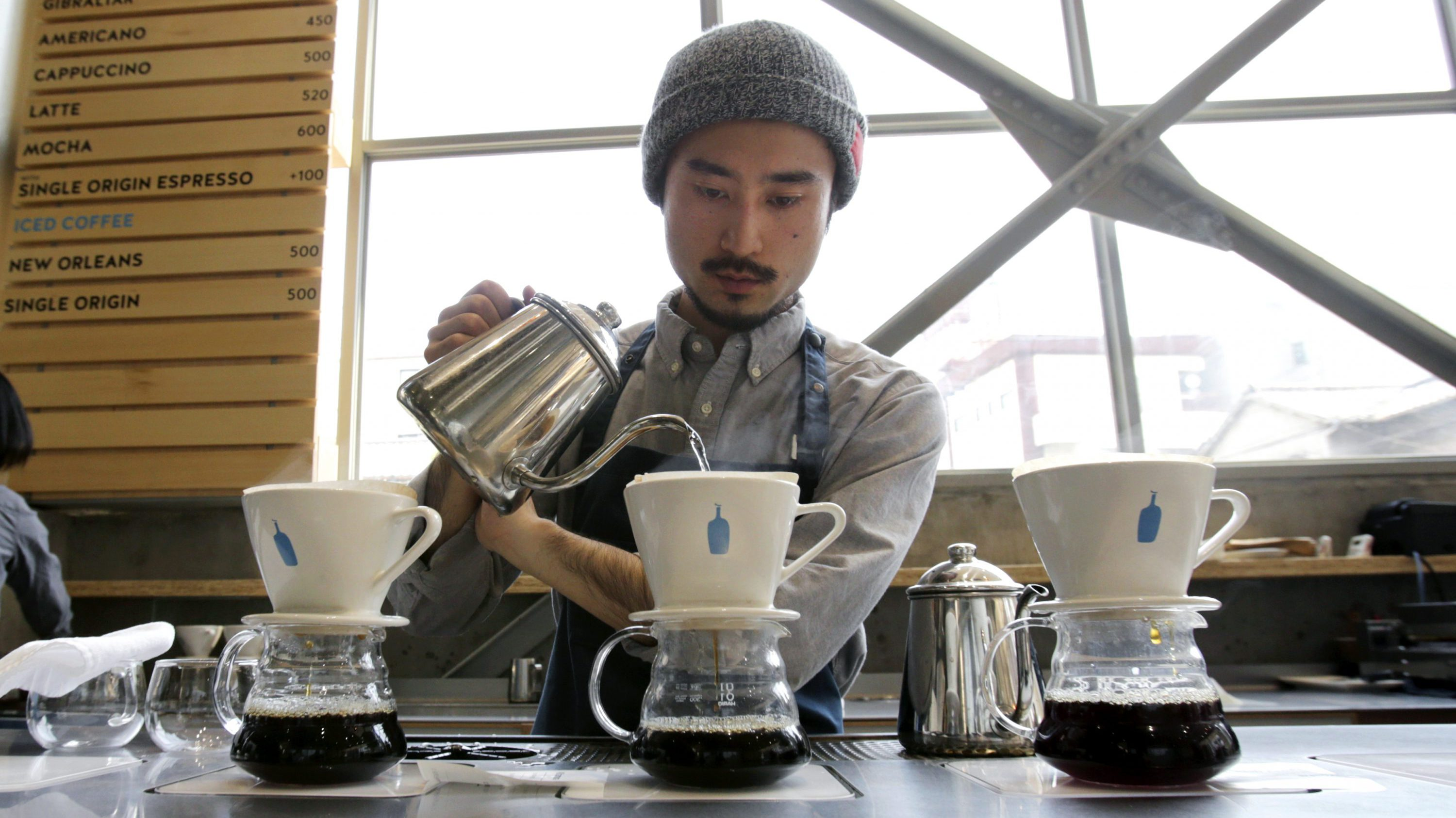 In this April 27, 2015 photo, a barista brews coffee at a Blue Bottle Coffee shop in Tokyo. Japan, famous for green tea, is welcoming artisanal American coffee roaster Blue Bottle with long lines that have at times meant a four-hour wait for a cup.