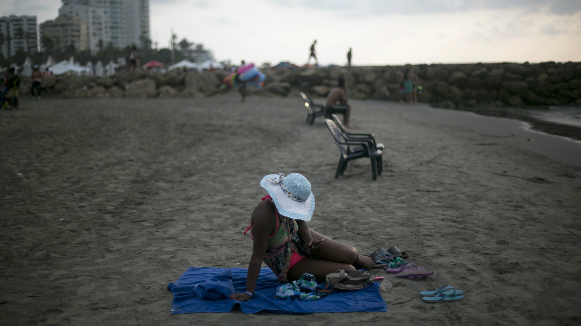 A woman uses her cell phone as she sits on the beach in Cartagena, Colombia, Tuesday, Sept. 27, 2016, the day after the government signed a peace agreement with the Revolutionary Armed Forces of Colombia, FARC, to end over 50 years of conflict.