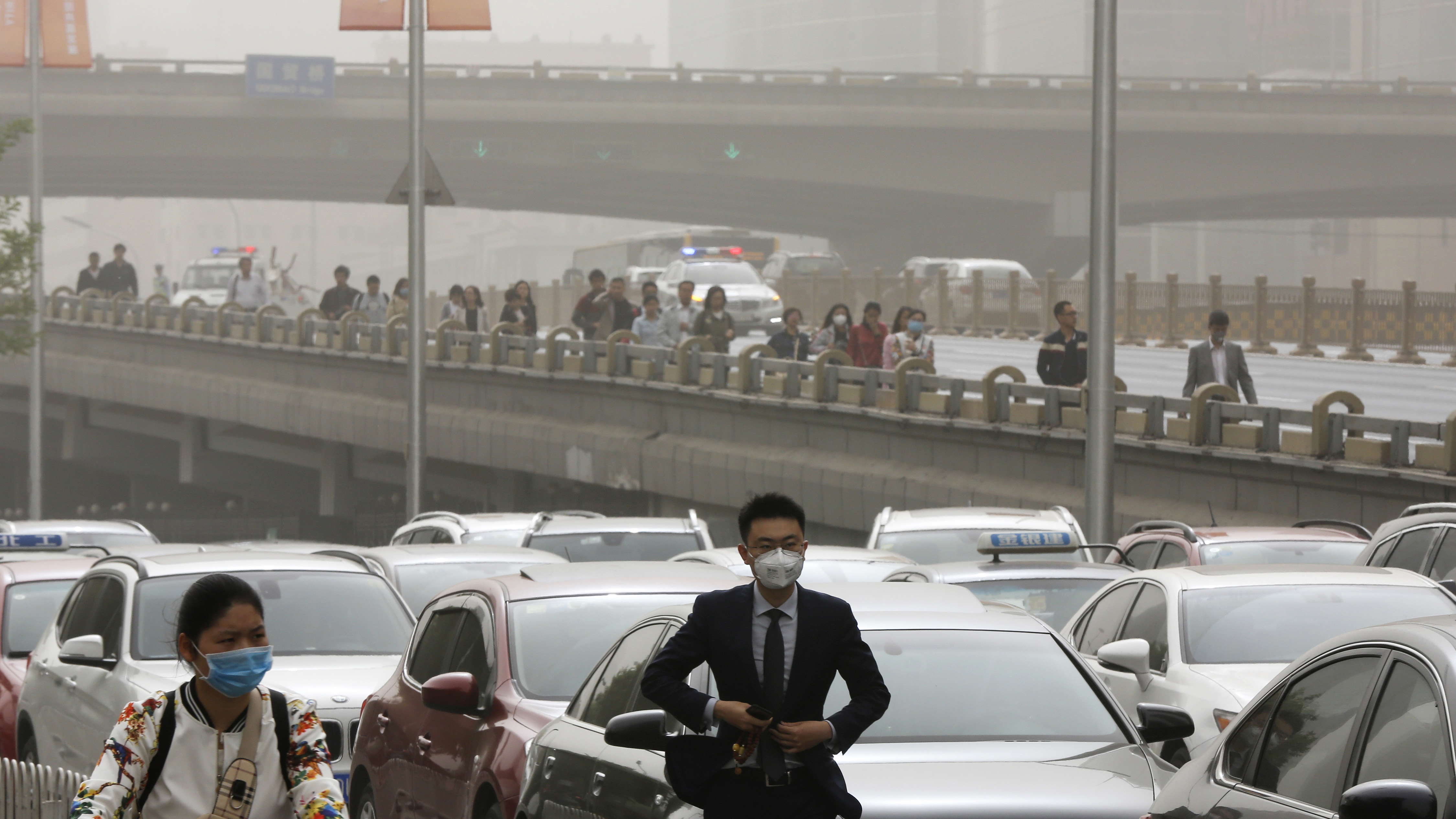 People wearing face masks walk past cars clogged with heavy traffic on a road as Beijing is hit by polluted air and sandstorm Thursday, May 4, 2017. Authorities in Beijing issued a blue alert on air pollution as sandstorm swept through the Chinese capital city on Thursday morning. (AP Photo/Andy Wong)