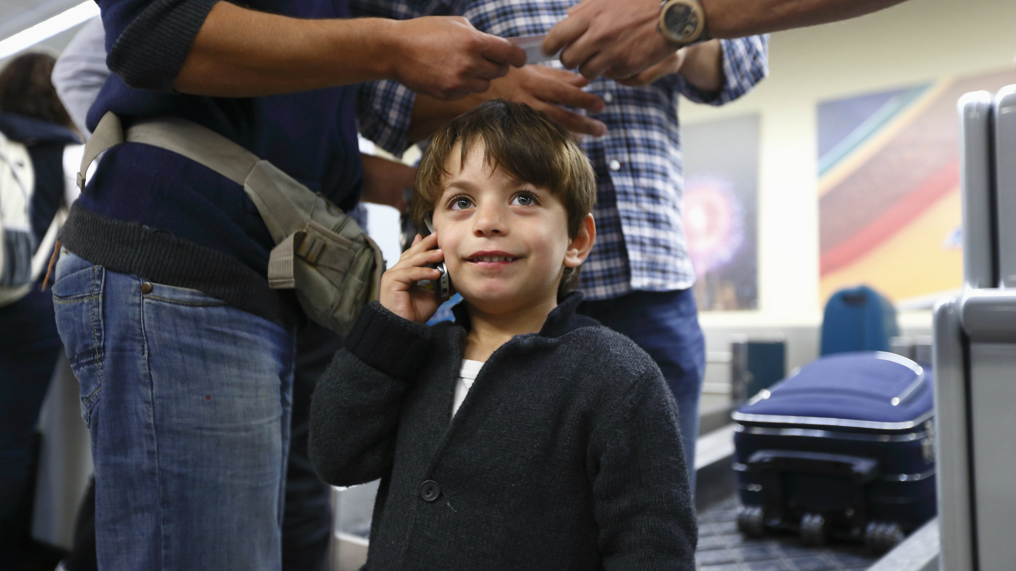Syrian shipwreck survivor Haider, 4, talks on a phone as a police officer hands boarding passes to his father Hatim Shabar (L), after checking in for a flight to Sicily at Malta International Airport outside Valletta November 6, 2013. Both refugees were rescued and brought to Malta after their boat capsized 60 miles south of Lampedusa last month, leaving between 50 and 200 Syrian and Palestinian migrants dead, according to local media. They will be reunited with Haider's seven-year-old brother, who had been taken to Lampedusa after the shipwreck, in Sicily later today, according to the UNHCR. His two other brothers and mother remain missing, believed drowned.  REUTERS/Darrin Zammit Lupi (MALTA - Tags: SOCIETY IMMIGRATION DISASTER) MALTA OUT. NO COMMERCIAL OR EDITORIAL SALES IN MALTA