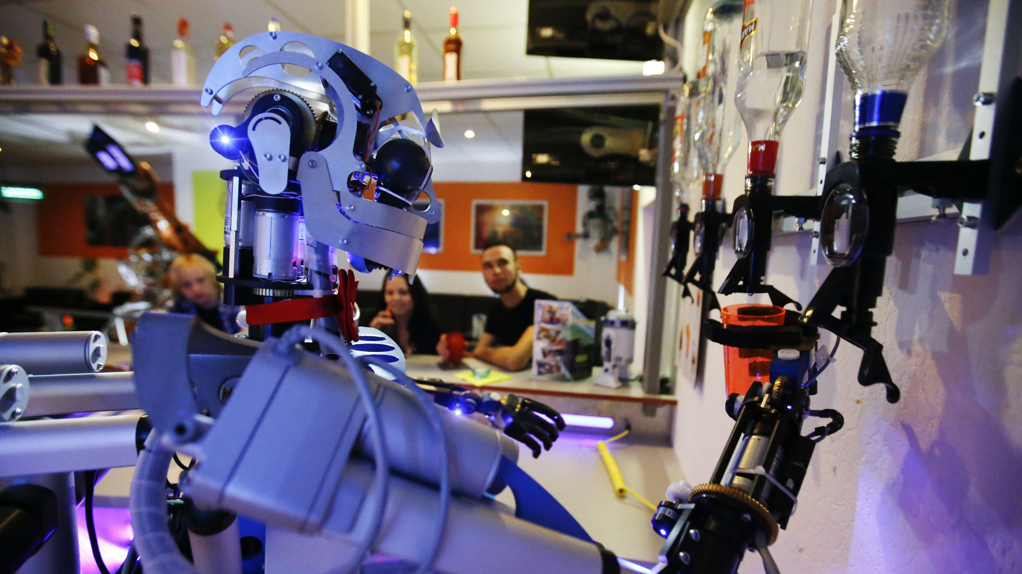 "prepare a drink for a guest at the Robots Bar and Lounge in the eastern German town of Ilmenau, July 26, 2013. ""Carl"", developed and built by mechatronics engineer Ben Schaefer who runs a company for humanoid robots, prepares spirits for the mixing of cocktails and is able to interact with customers in small conversations. Picture taken July 26, 2013."