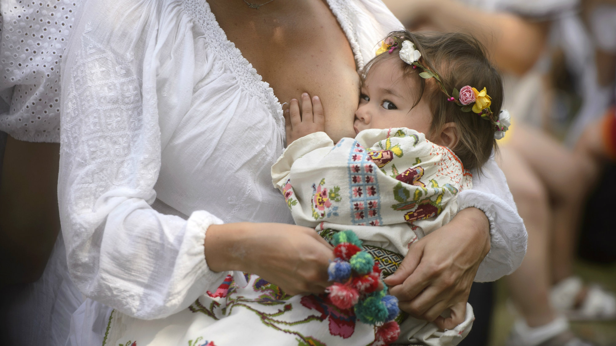 A woman breastfeeds her eighteen-month-old daughter Anastasia at an event promoting the freedom of mothers to breastfeed in public, during World Breastfeeding Week at the Village Museum in Bucharest, Romania, Saturday, Aug. 6, 2016.
