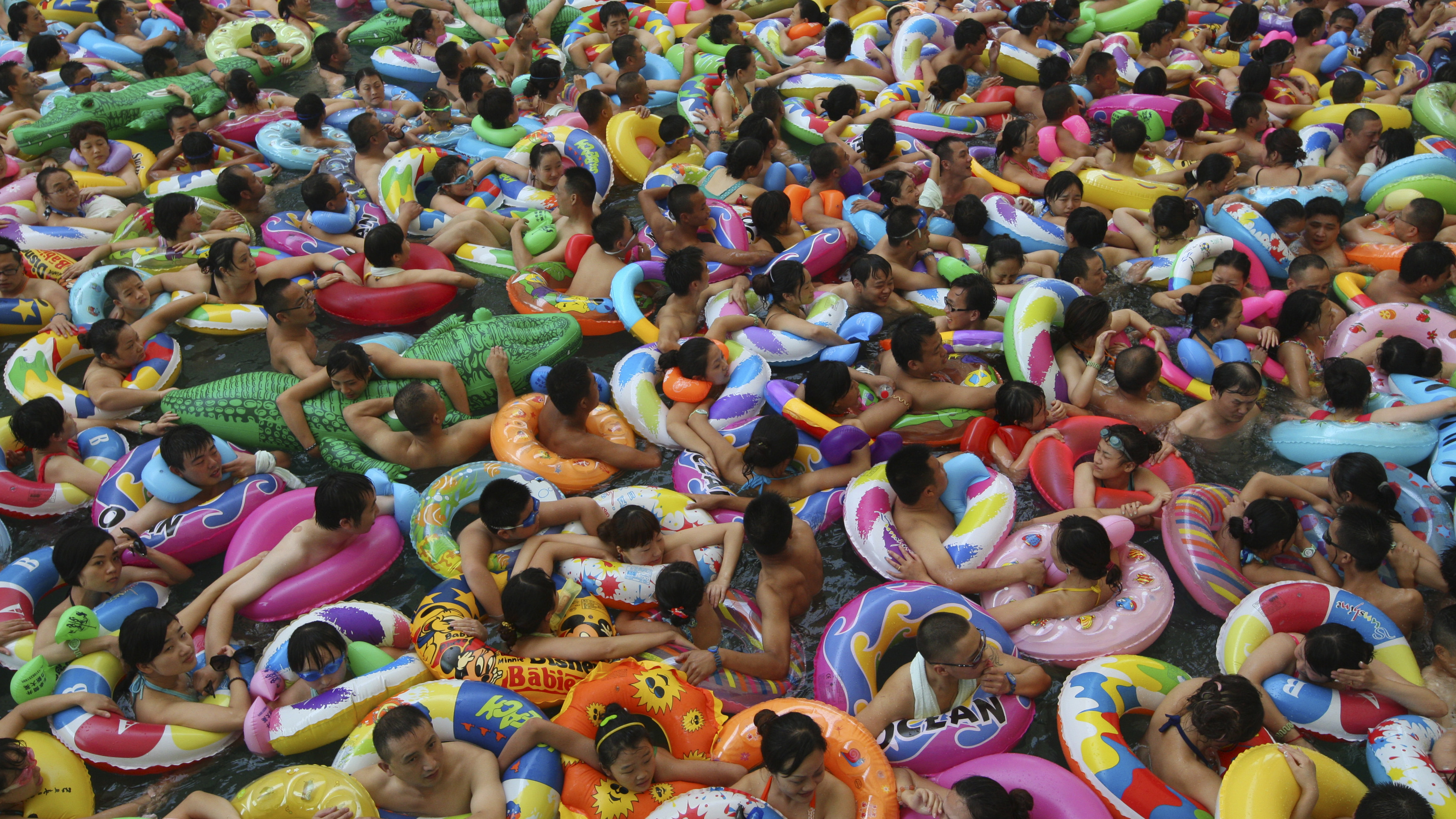 Visitors crowd an artificial wave pool at a tourist resort to escape the summer heat in Daying county of Suining, Sichuan province, July 27, 2013. Picture taken July 27, 2013. REUTERS/China Daily (CHINA - Tags: ENVIRONMENT TRAVEL SOCIETY TPX IMAGES OF THE DAY) CHINA OUT. NO COMMERCIAL OR EDITORIAL SALES IN CHINA - RTX1226J