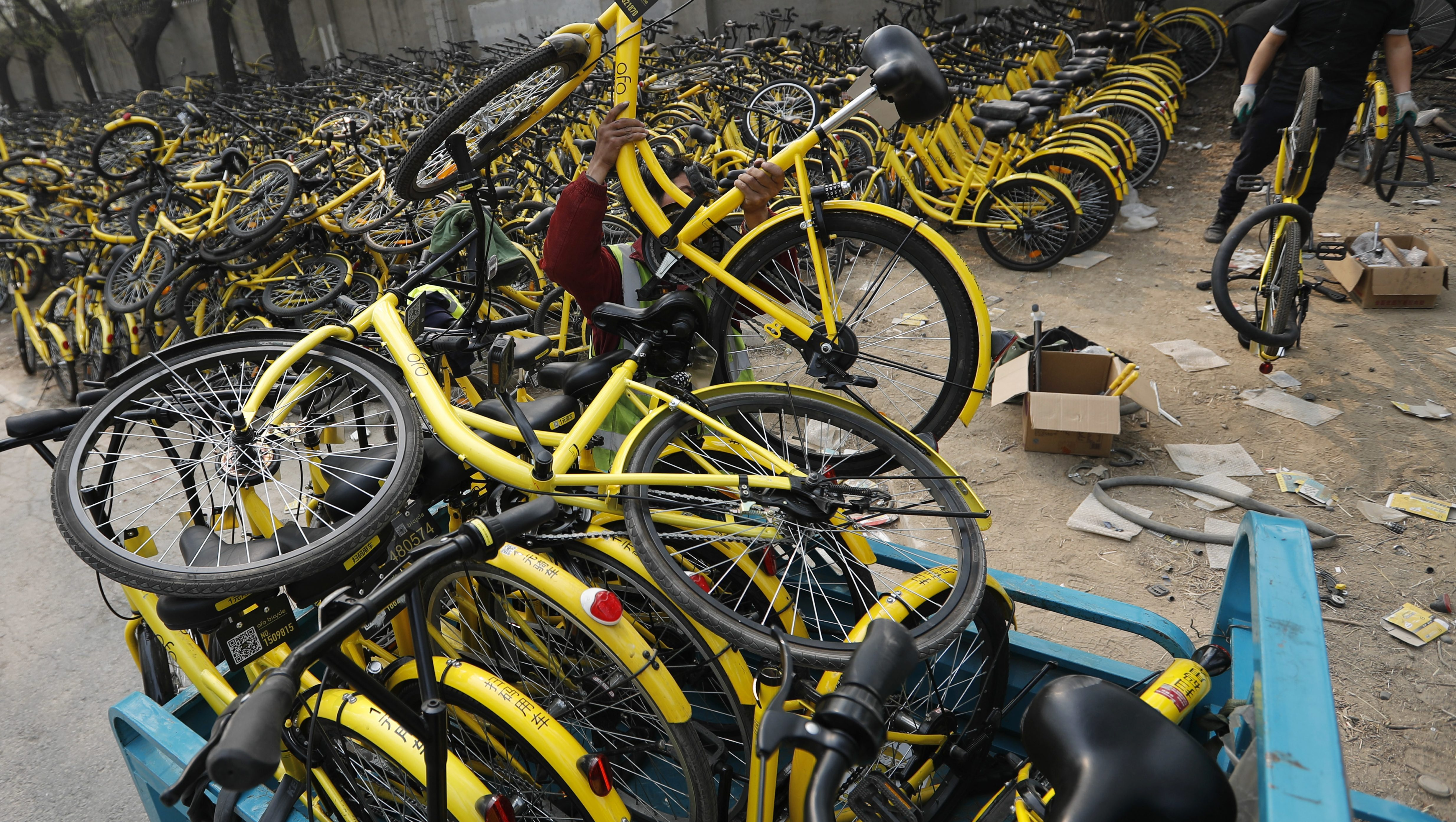 In this Sunday, March 19, 2017 photo, a worker from the bike-sharing company Ofo unloads damaged bicycles from a tricycle at a repair station in Beijing, China. As many as 2.2 million of these two-wheelers have been deployed, which are available for rent for as little as 7 cents a ride, in the latest symbol of heavy spending in China's internet sector where startups are in a race to attract more users to their services. (AP Photo/Andy Wong)