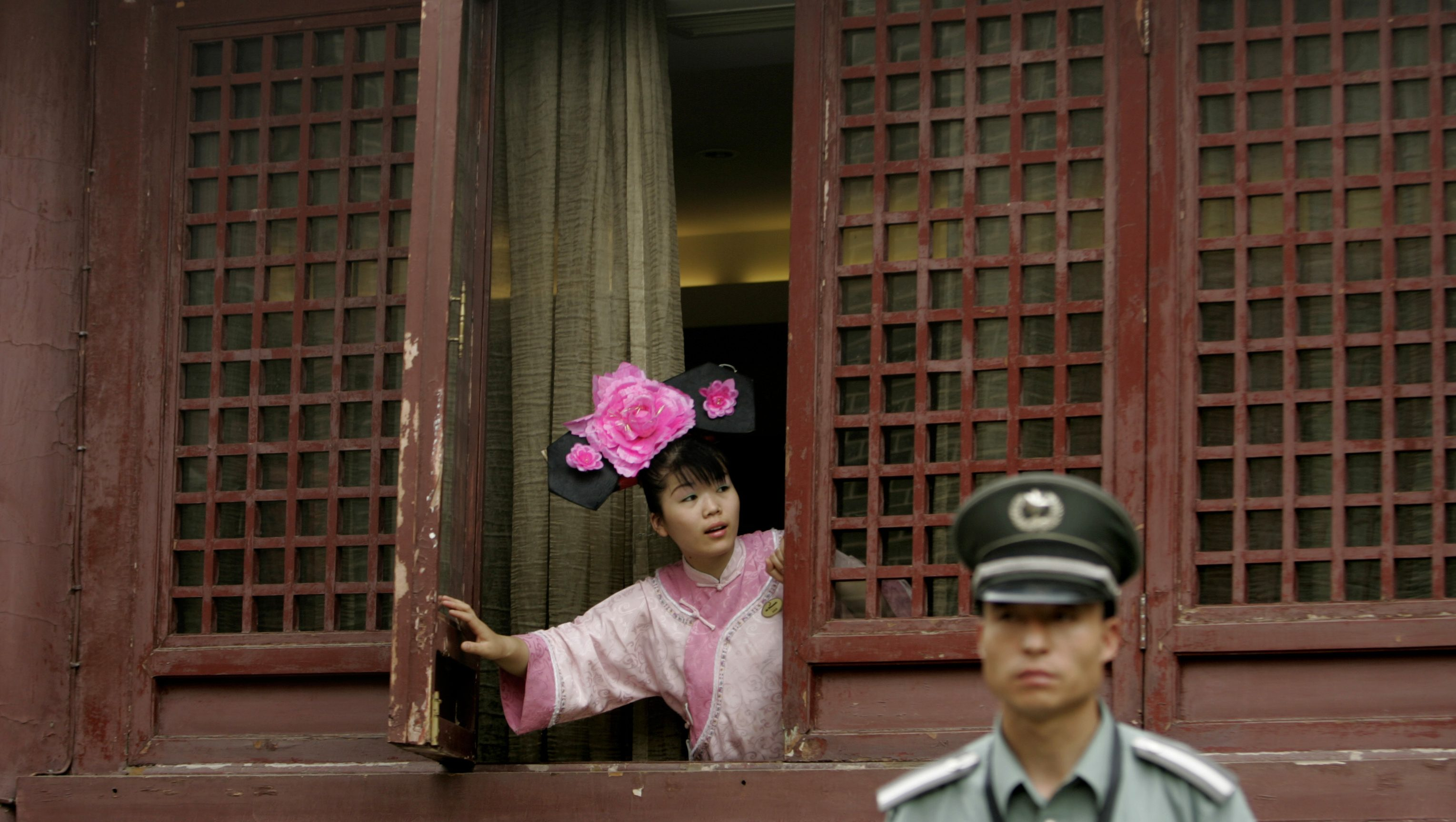 A waitress, dressed as a Qing dynasty lady-in-waiting, looks out from a window as a security guard stands nearby at the Beijing Jun hotel in Beijing May 30, 2007. The courtyard hotel was built in Qing Dynasty-style architecture.