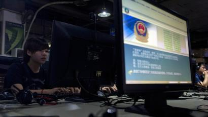 FILE - In this Aug. 19, 2013 file photo, computer users sit near a monitor display with a message from the Chinese police on the proper use of the Internet at an Internet cafe in Beijing, China. China is blocking VPN services that let users skirt online censorship of popular websites such as Google and Facebook amid a wider crackdown on online information, tech companies and specialists said Friday, Jan. 23, 2015. The virtual private network provider Golden Frog wrote on its blog that the controls have hit a wide swath of VPN services. The popular provider Astrill informed its users this week that the controls have started hitting iPhone access to services such as Gmail. (AP Photo/Ng Han Guan, File)
