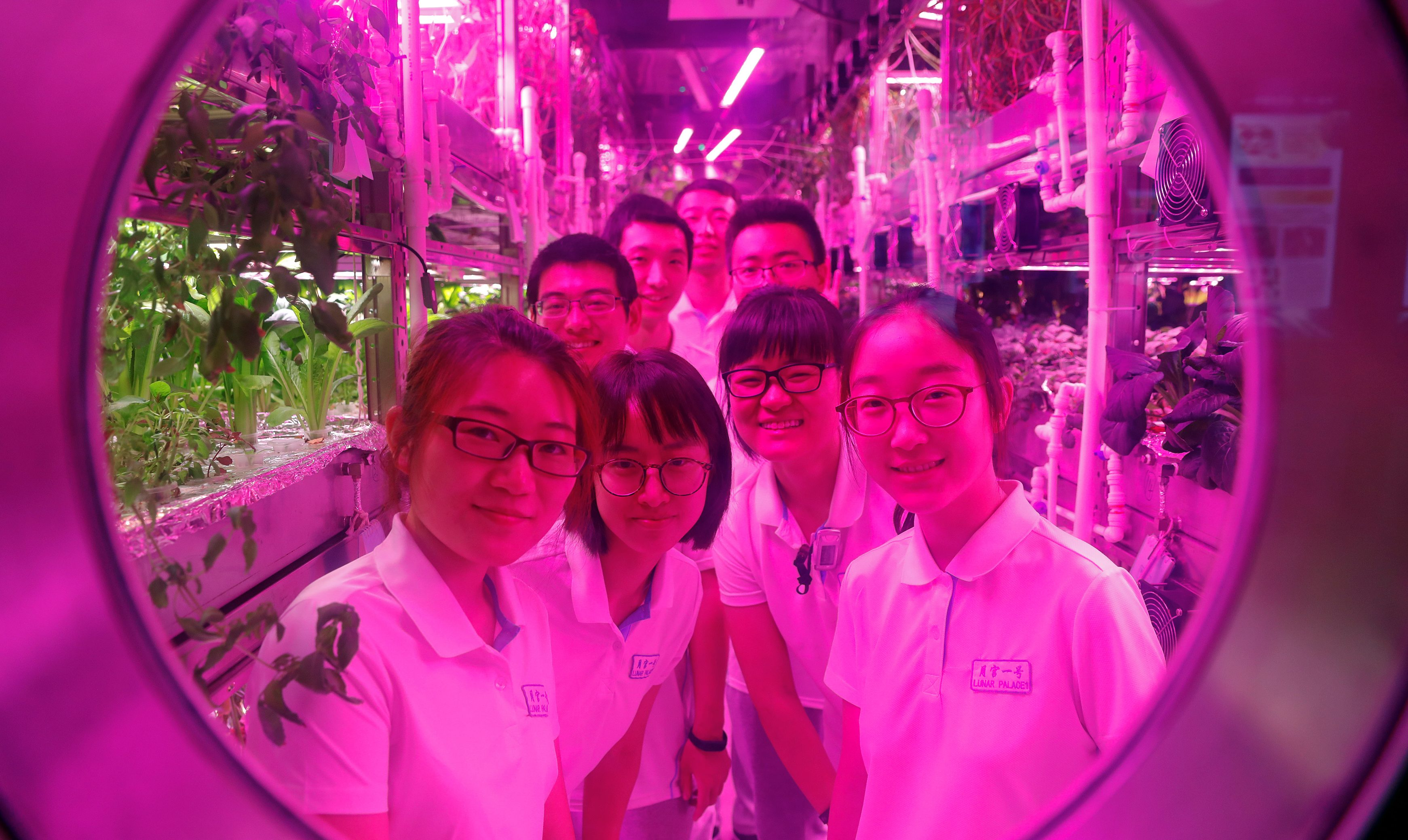 Volunteers smile from inside a simulated space cabin in which they temporarily live as a part of the scientistic Lunar Palace 365 Project, at Beihang University in Beijing, China July 9, 2017. A group of four volunteers entered the Lunar Palace, a space of 160 square meters, China's first bioregenerative life-support base where they will live for next 200 days replacing another group who spent previous 60 days inside the simulated cabin testing how a life-support system works in a moon-like environment.