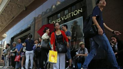 Chinese tourists wait for their bus in front of a fashion store in Paris, Wednesday, Aug. 12, 2015. China's currency fell further Wednesday following a surprise change in its exchange rate mechanism that rattled global markets and threatens to fan trade tensions with the United States and Europe. The central bank said the yuan's 1.9 percent devaluation Tuesday against the U.S. dollar, which was its biggest one-day fall in a decade, was due to changes aimed at making the tightly controlled currency more market-oriented. (AP Photo/Francois Mori)