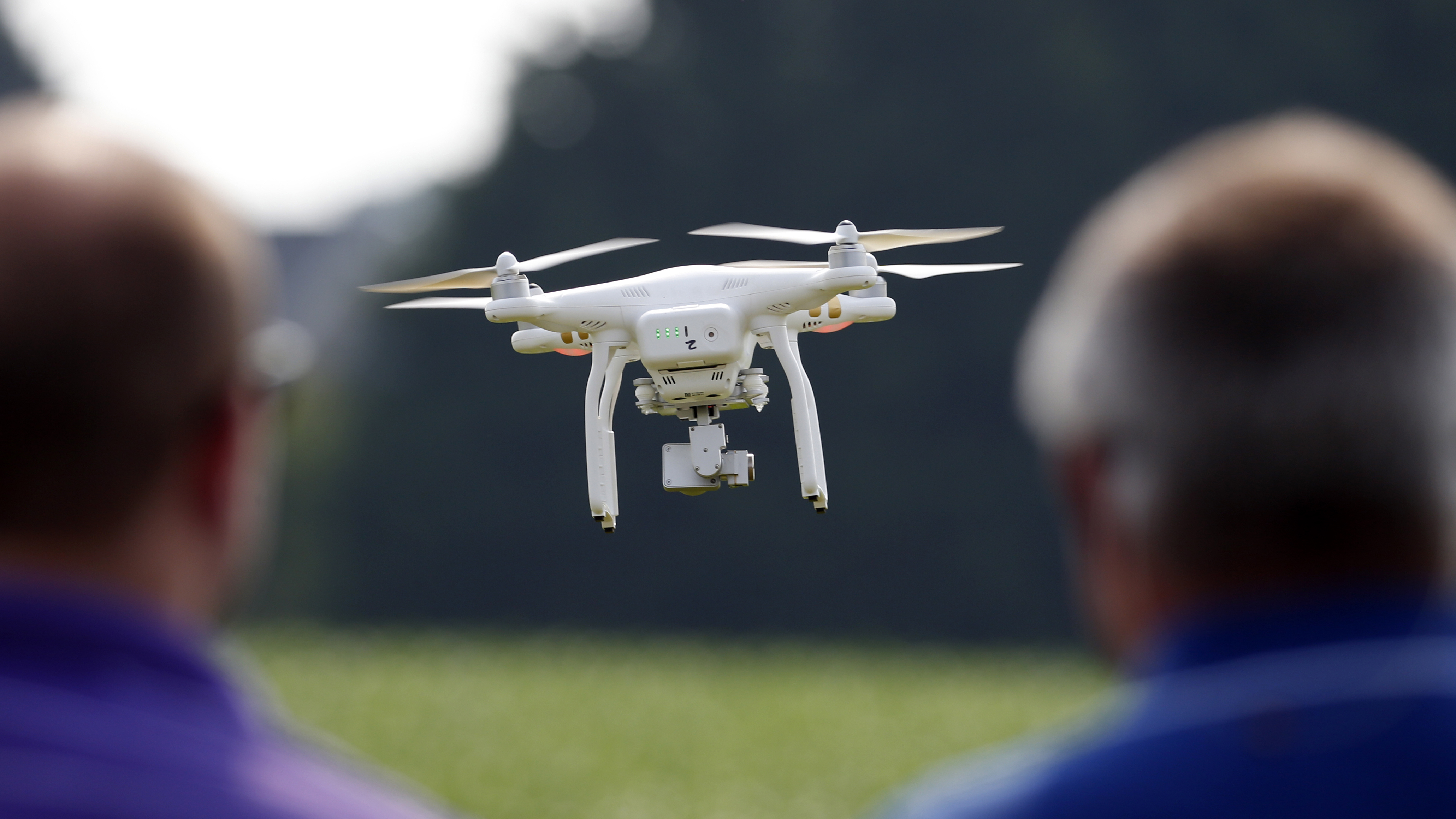 A DJI Phantom 3 drone is flown by Matthew Creger, left, marketing director for Intelligent UAS, as he talks with Chip Bowling, from Newburg, Md., president of the National Corn Growers, during a drone demonstration at a farm and winery, on potential use for board members of the National Corn Growers, Thursday, June 11, 2015 in Cordova, Md. (AP Photo/Alex Brandon)