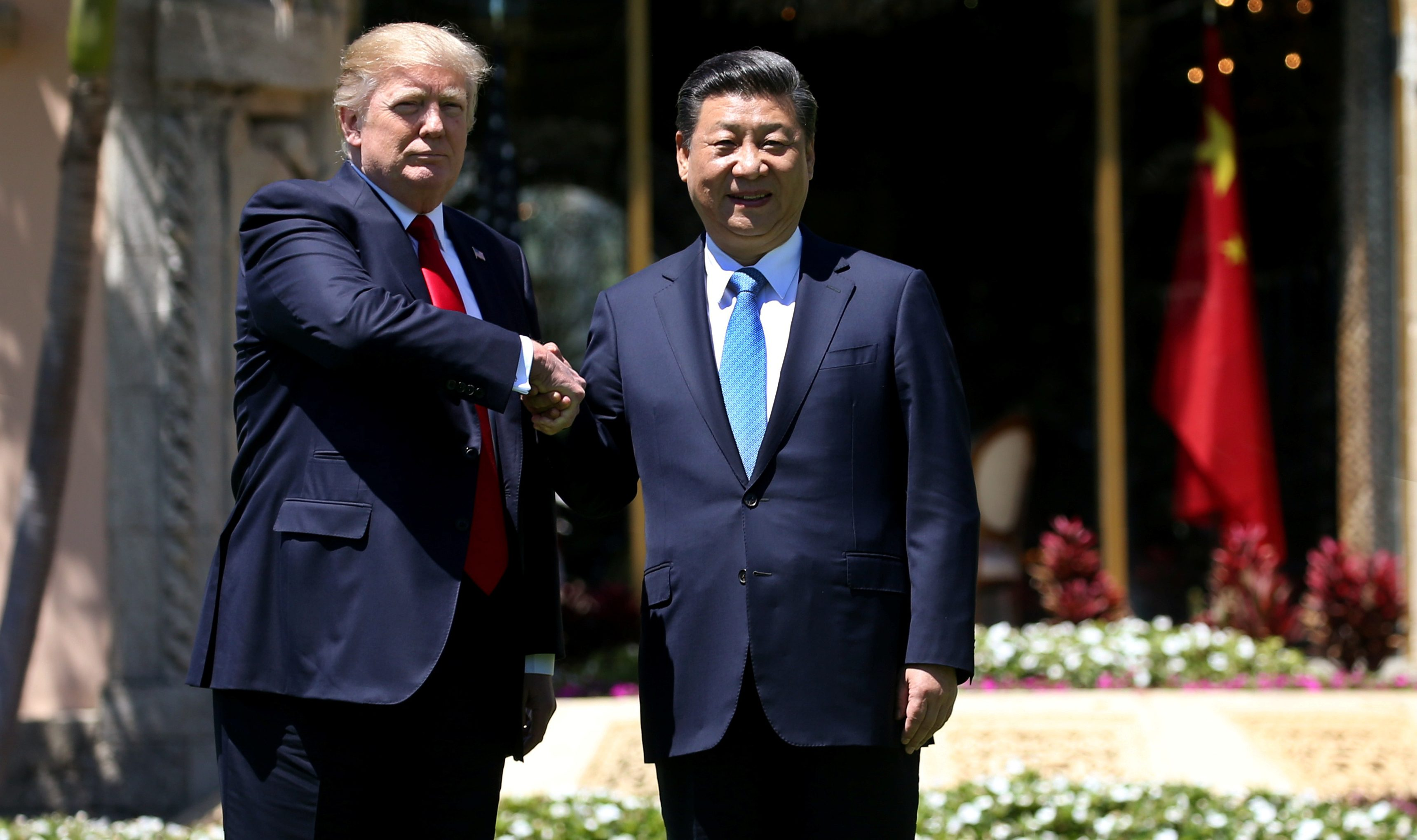 U.S. President Donald Trump (L) and China's President Xi Jinping shake hands while walking at Mar-a-Lago estate after a bilateral meeting in Palm Beach, Florida, U.S., April 7, 2017. REUTERS/Carlos Barria - RTX34MII