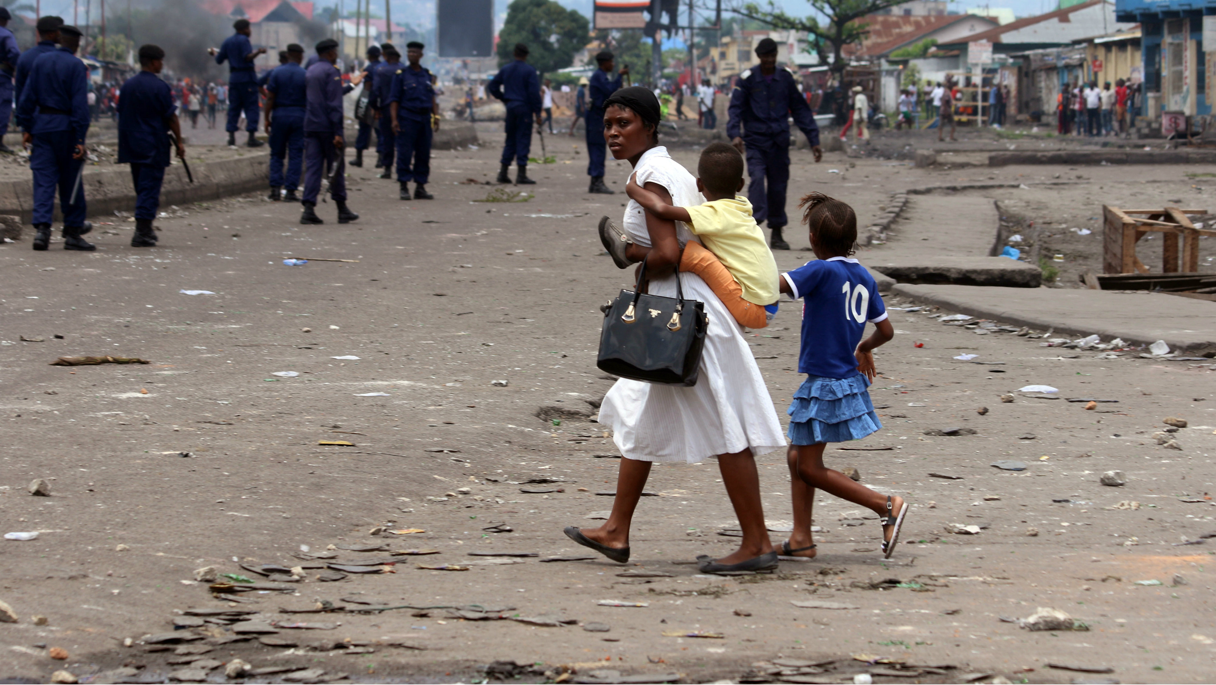 A family pass near Congolese riot police during a protest in Kinshasa, Democratic Republic of Congo, Monday, Sept. 19, 2016. Witnesses say at least four people are dead after opposition protests against a delayed presidential election turned violent in Congo's capital. The protests were organized by activists who are opposed to longtime President Joseph Kabila, who is now expected to stay in office after his mandate ends in December.