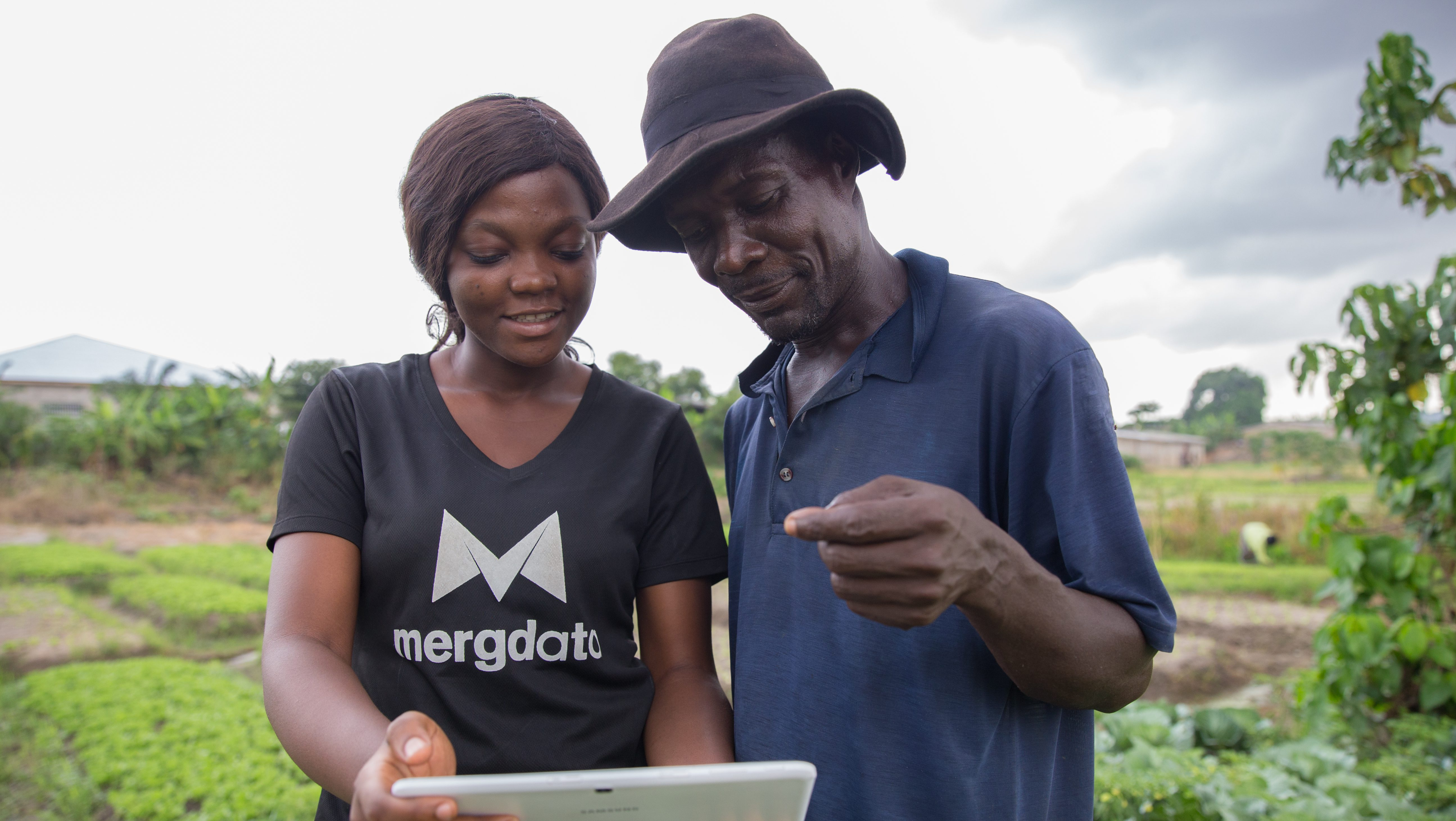 Bernice Adu-Boahen from Farmerline explains to Sam Emmanuel how the Mergdata service works at Sam's farm in Gyinase, Kumasi, Ghana. Mergdata gives farmers useful information like weather, market prices and farming tips on their mobile phones to help them improve their harvest and get the best prices for it.