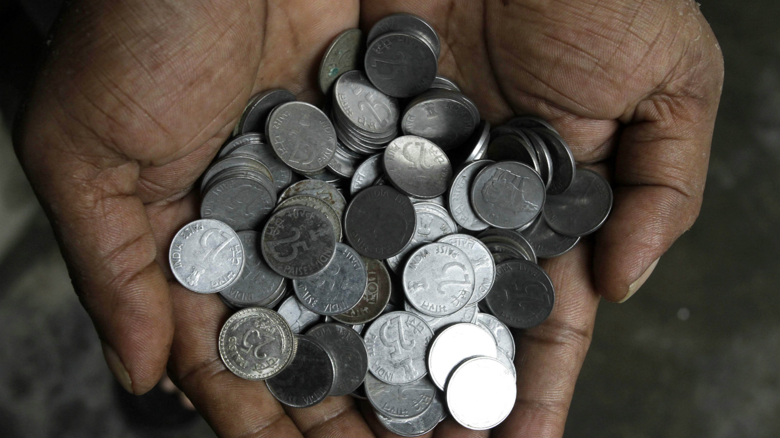 A man shows handful of Indian 25 paisa (US $ 0.005) coins prior to deposit at bank for exchange, in Kolkata, India, Wednesday, June 29, 2011. The Reserve Bank of India is withdrawing 25 paise coins and those of lower denomination from the market with effect from June 30. These coins will not be in circulation and can't be used as legal tender for payment