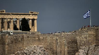 Greek flag in front of the ancient Parthenon temple