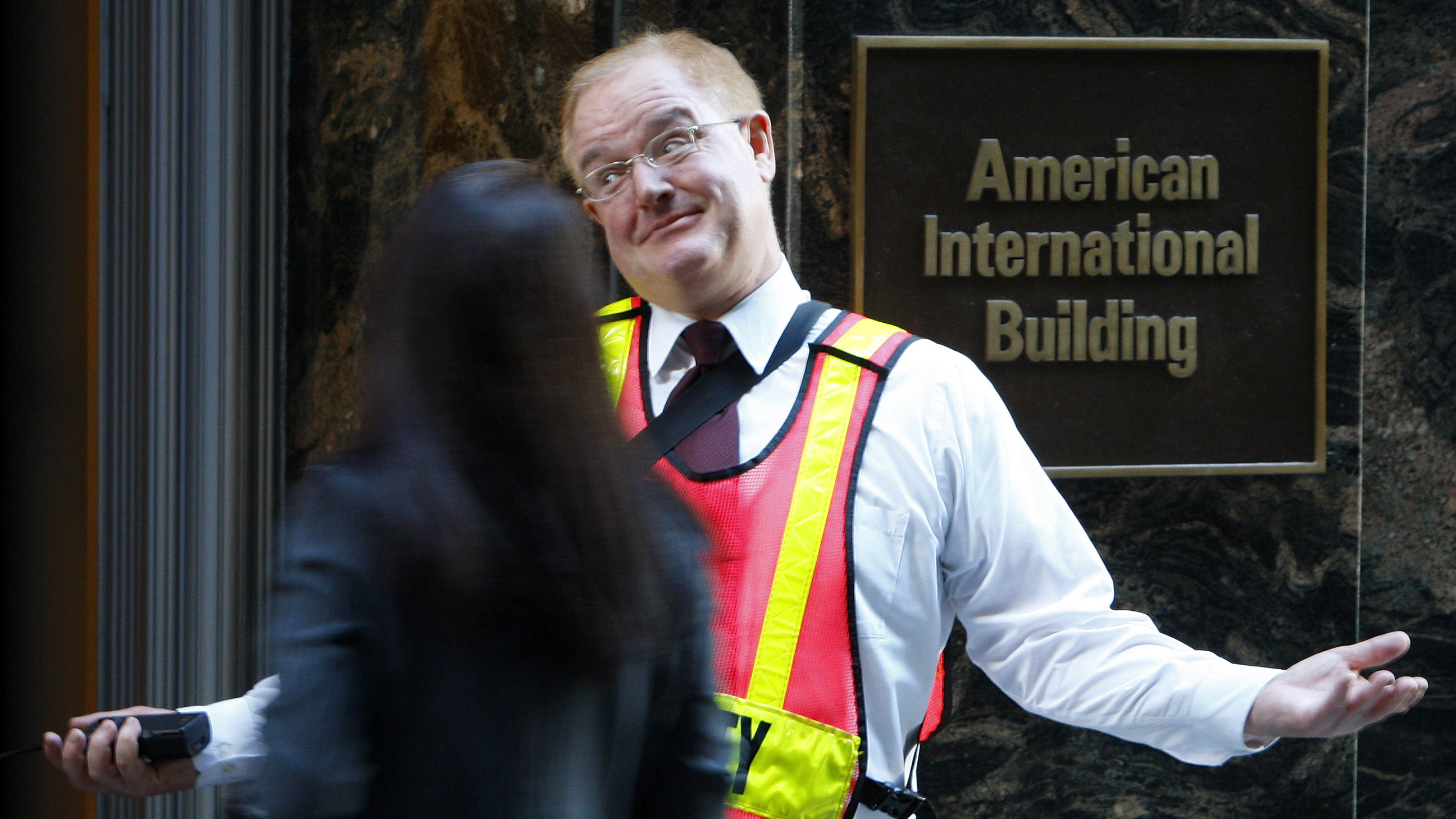 A security guard greets workers outside the AIG headquarters in New York's financial district September 15, 2008. Shares of American International Group fell more than 50 percent in early trading on reports that the insurer had turned to the Federal Reserve for $40 billion in bridge financing to ward off a liquidity crisis and ratings downgrades. REUTERS/Brendan McDermid