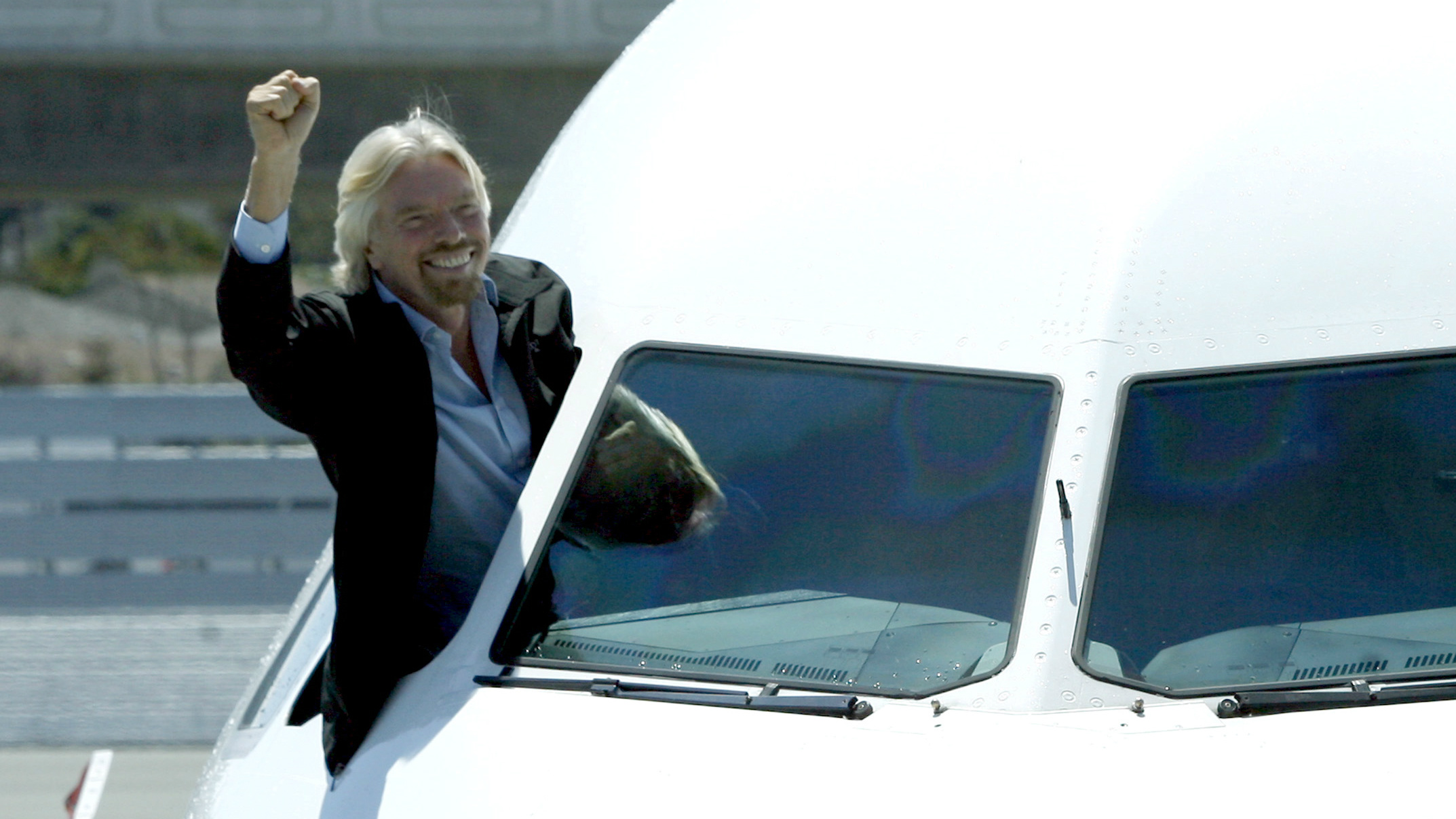 Richard Branson waves from the cockpit of a plane