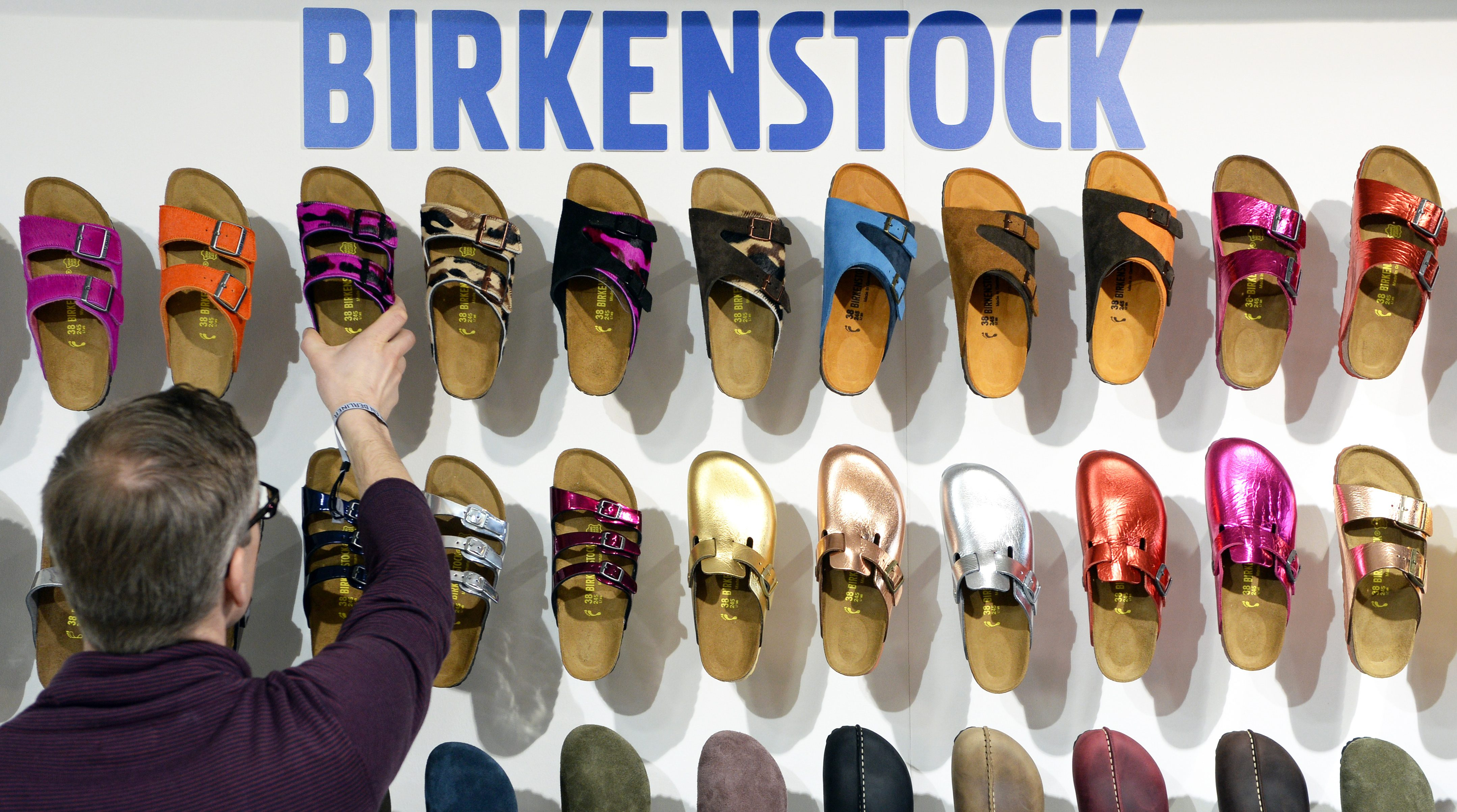 A employee arranges shoes of German label Birkenstock during the fashion fair 'Bread & Butter' in the former Tempelhof airport in Berlin, Germany, 14 January 2014. 'B&B' takes place during the Berlin Fashion Week that presents the Autumn/Winter 2014/2015 collections and runs from 11 to 14 January. EPA/SOEREN STACHE