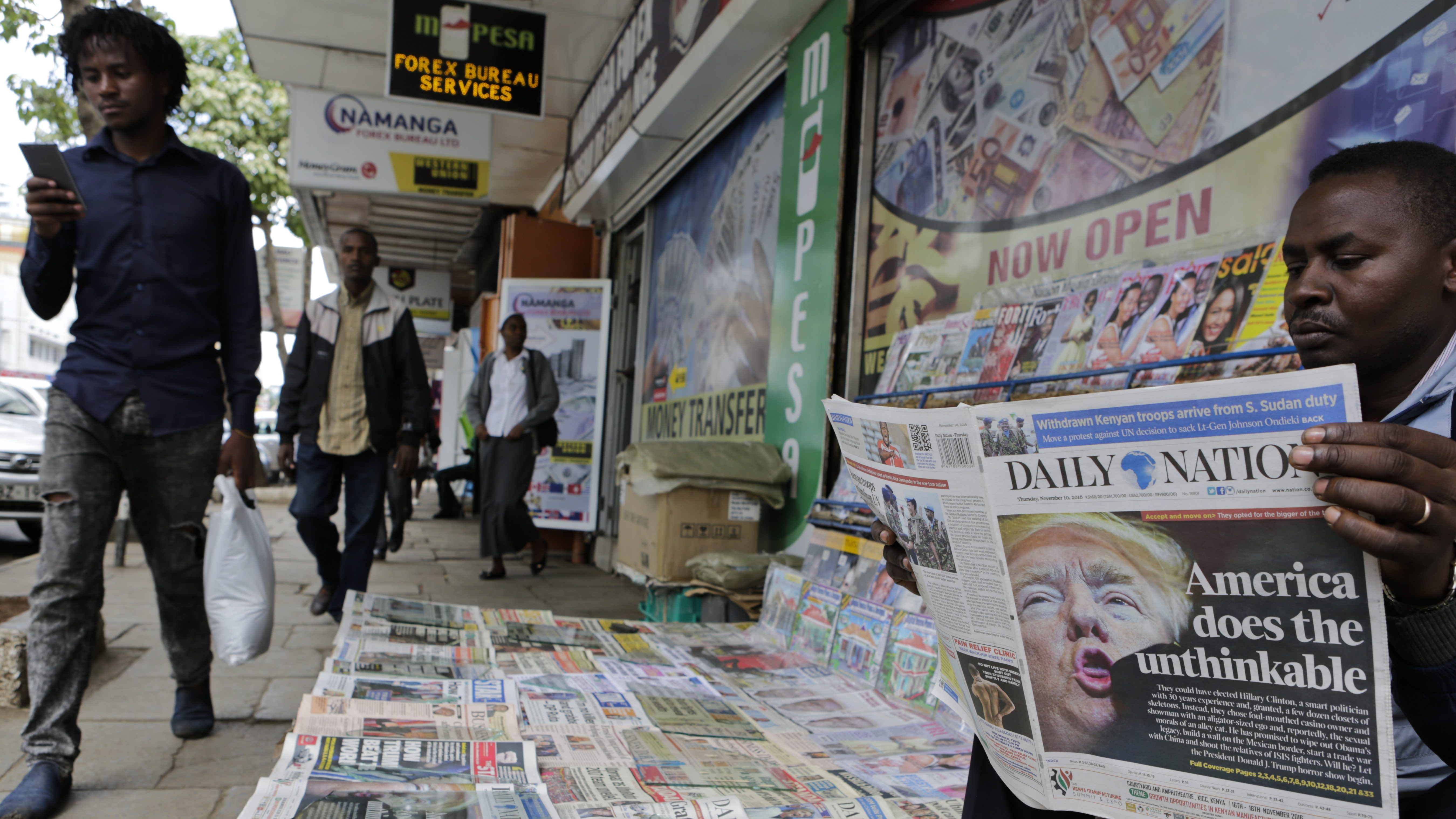 epa05625379 A Kenyan newspaper vendor (R) reads a newspaper featuring front page article about US President-elect Donald Trump as he waits for customers at a street in Nairobi, Kenya, 10 November 2016. Americans on 08 November chose Republican candidate Donald Trump as the 45th President of the United States of America, to serve from 2017 through 2020.