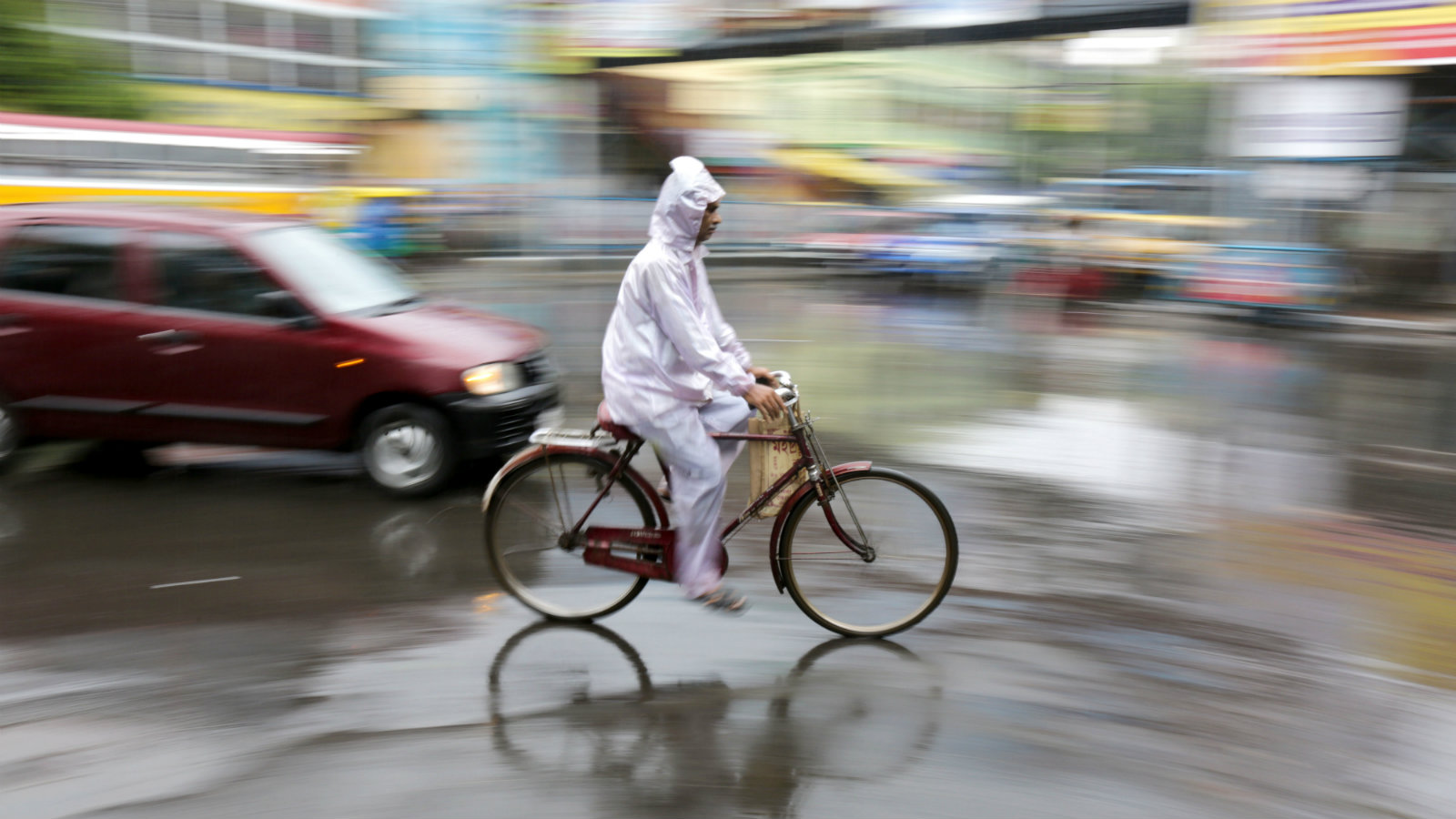 An Indian commuters rides a bicycle during monsoon showers in Calcutta, eastern India, 22 August 2016. A monsoon shower hit the city and disrupted daily life. The Indian monsoon season usually takes place between May and September.