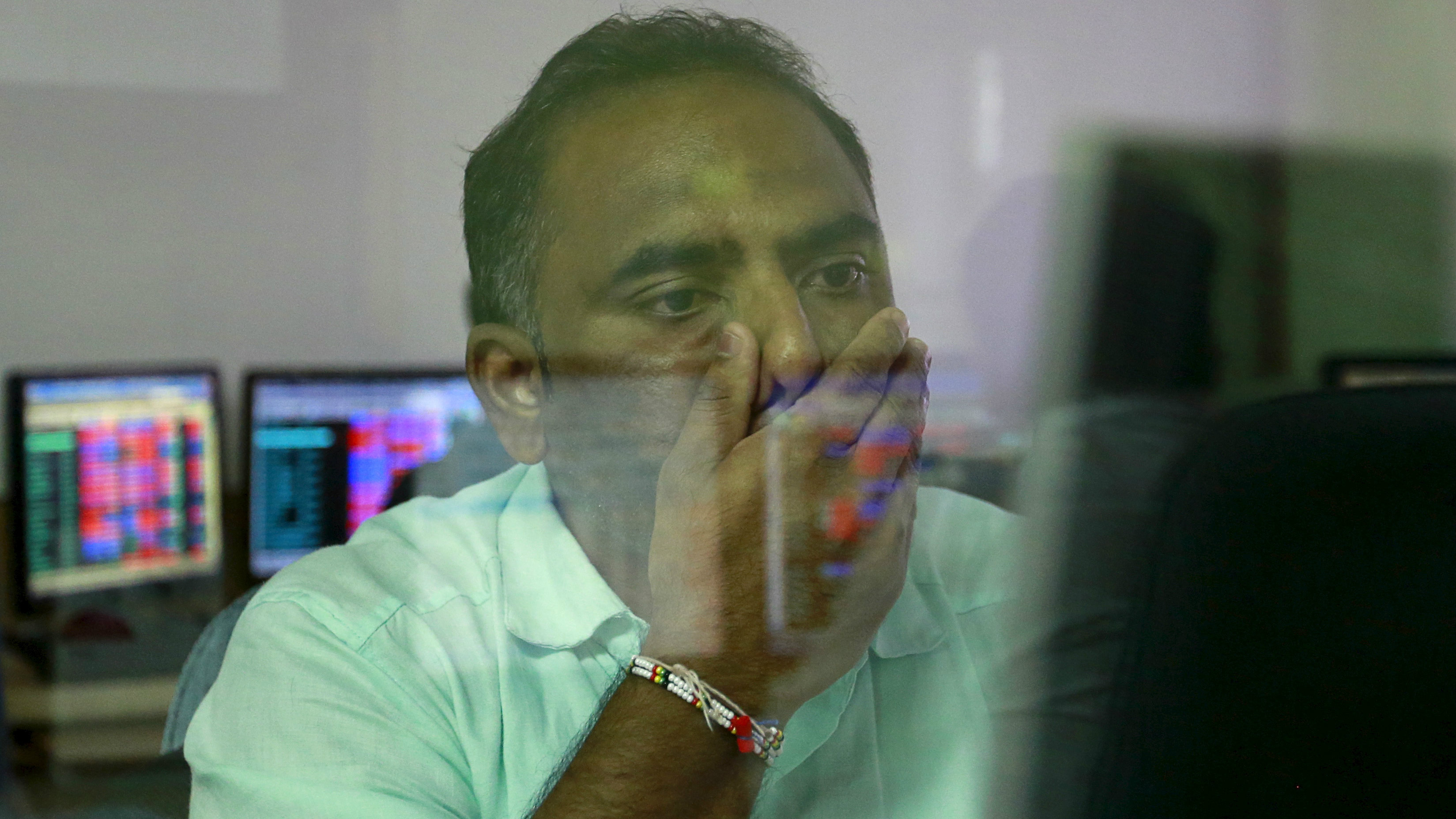 A broker reacts while trading at his computer terminal at a stock brokerage firm in Mumbai, India, August 24, 2015. India's benchmark BSE index fell more than 5 percent on Monday to their lowest in a year, as a rout in Chinese equities sparked widespread unrest in global financial markets.