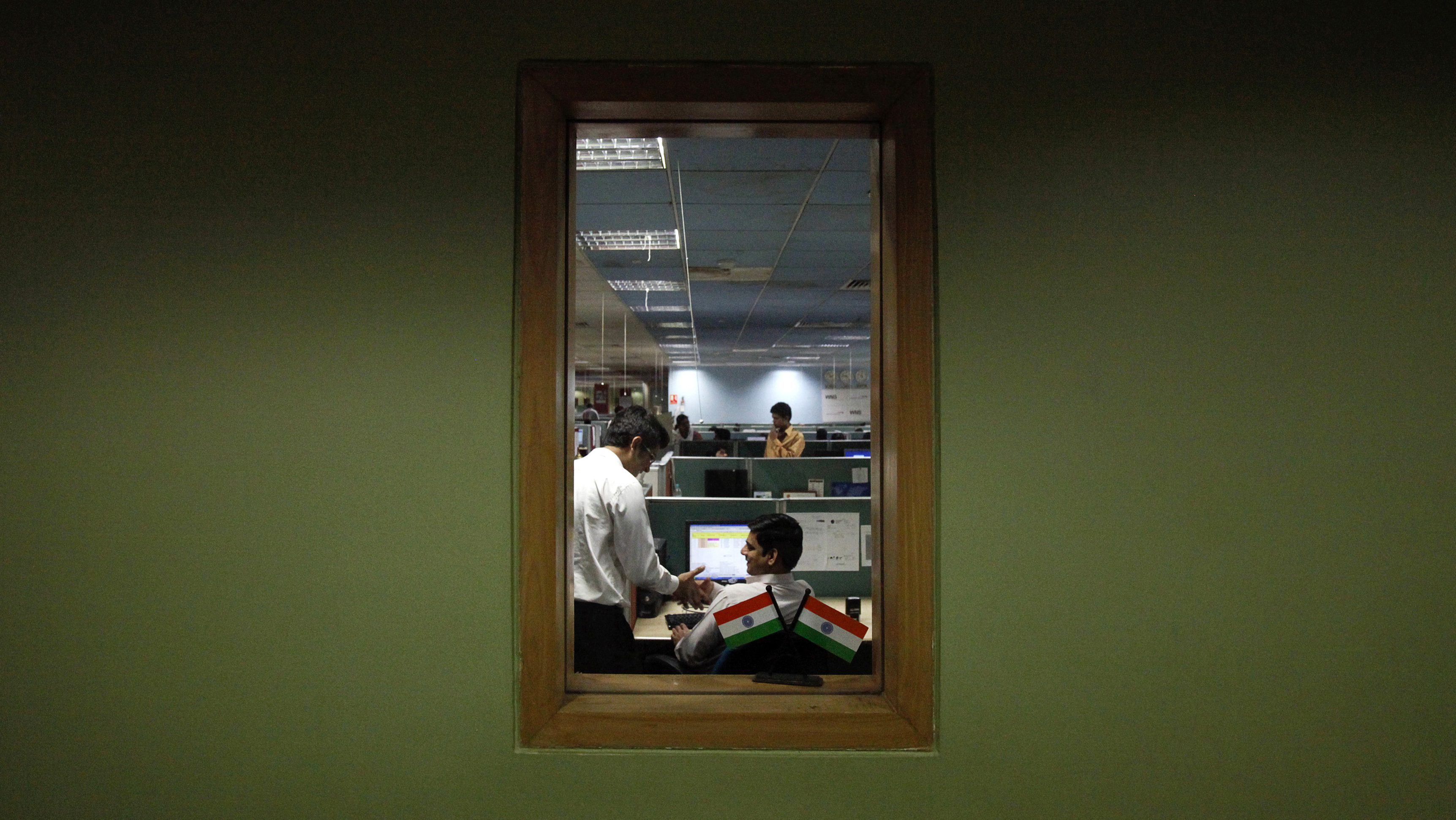 Employees are pictured through a window as they work on the floor of the outsourcing company WNS in Mumbai March 19, 2012.