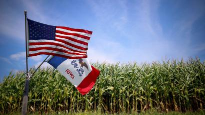 U.S. and Iowa state flags are seen next to a corn field