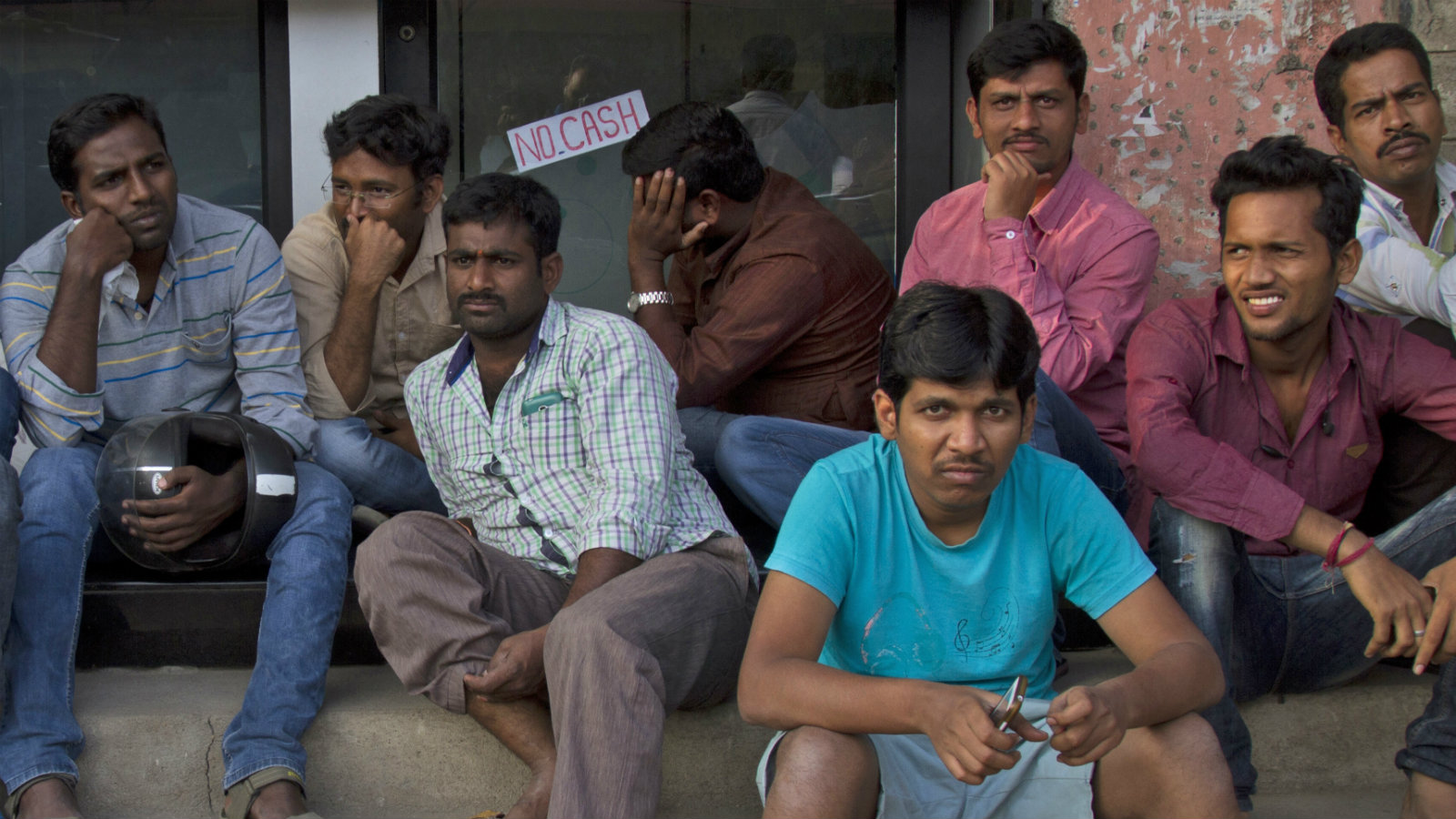 Indians wait outside a closed ATM to withdraw money in Hyderabad, India, Friday, Dec. 2, 2016. Indian Prime Minister Narendra Modi, in his Nov. 8 televised address, announced demonetization of India's 500 and 1,000-rupee notes, which made up 86 percent of the country's currency. People have been forced to stand in long queues to change banned notes and also to take out new currency from their accounts after severe limitations were imposed on withdrawal from banks and ATMs