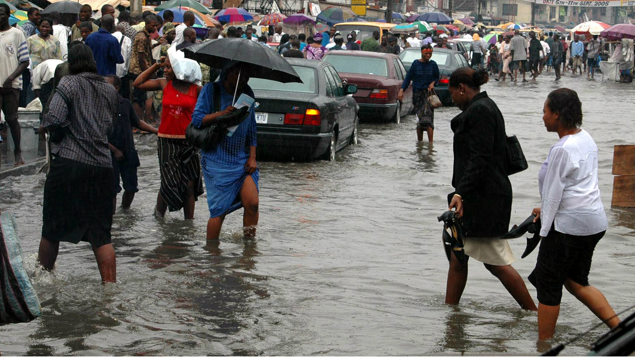 Residents cross a flooded street during rainfall in Lagos, Nigeria May 16, 2006.
