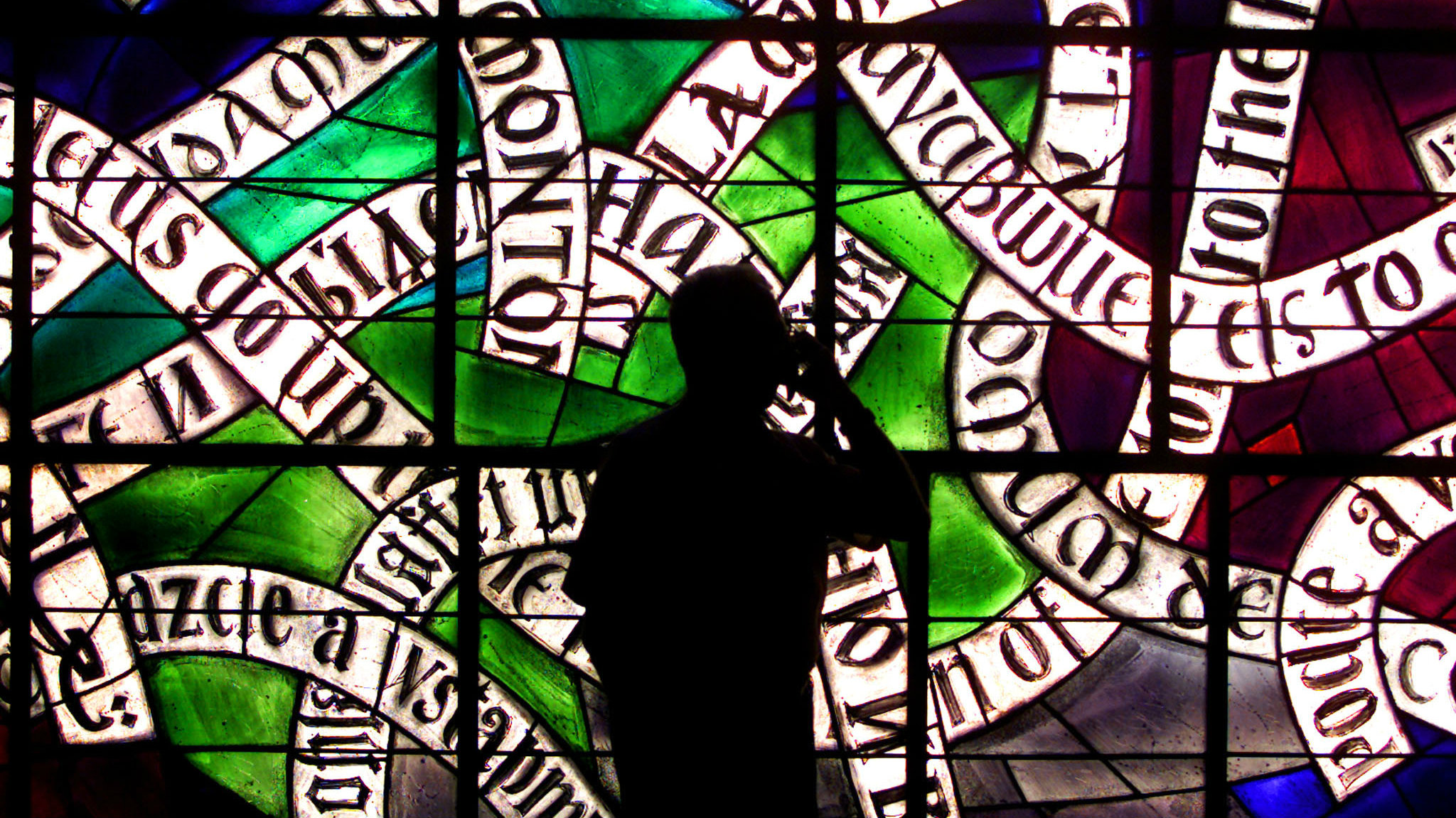 Man talking in front of stained glass window.