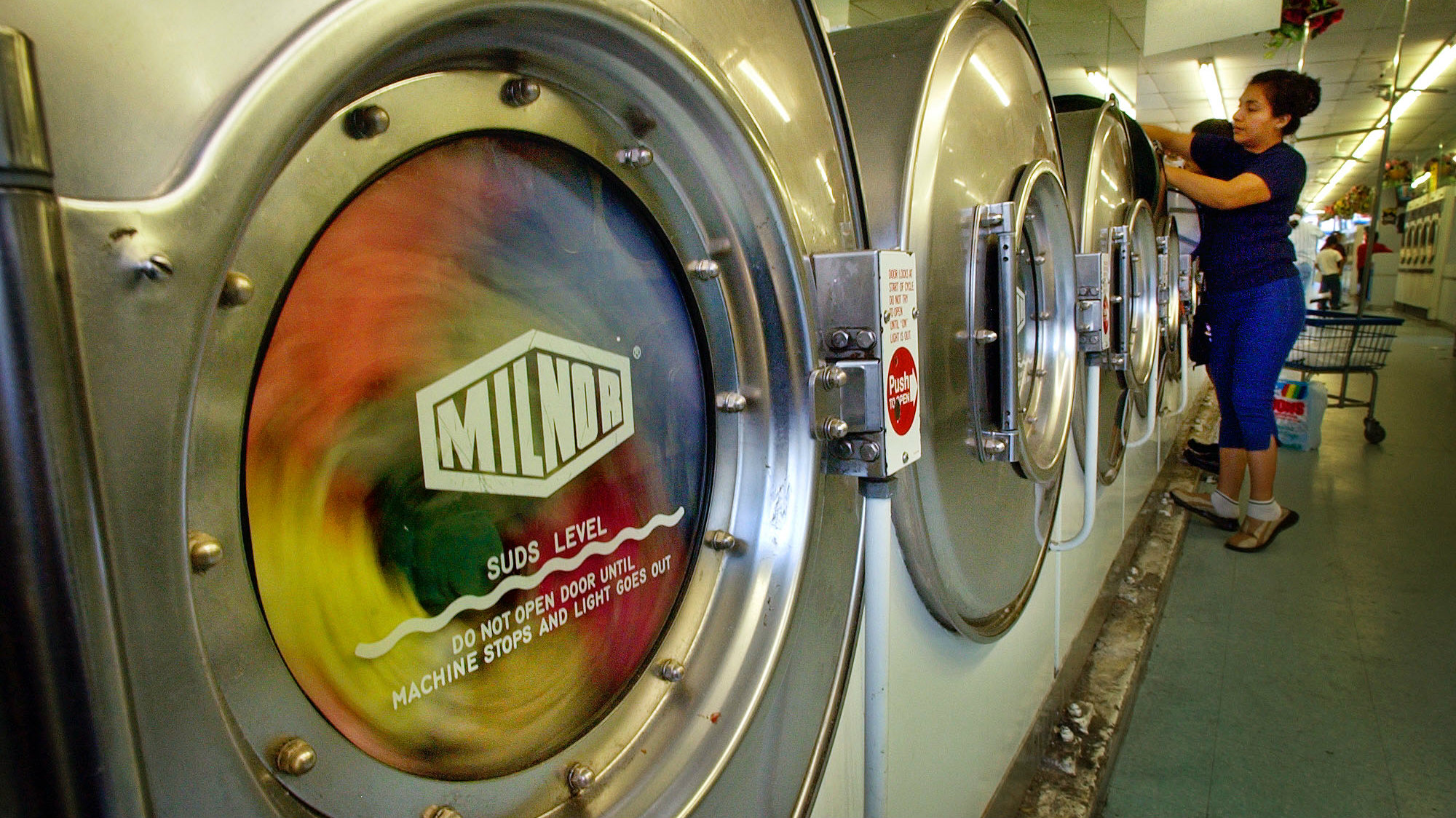 An unidentified woman loads clothes into a washing machine at a coin-operated laundry in Los Angeles' Echo Park district, Wednesday, Dec. 10, 2003.