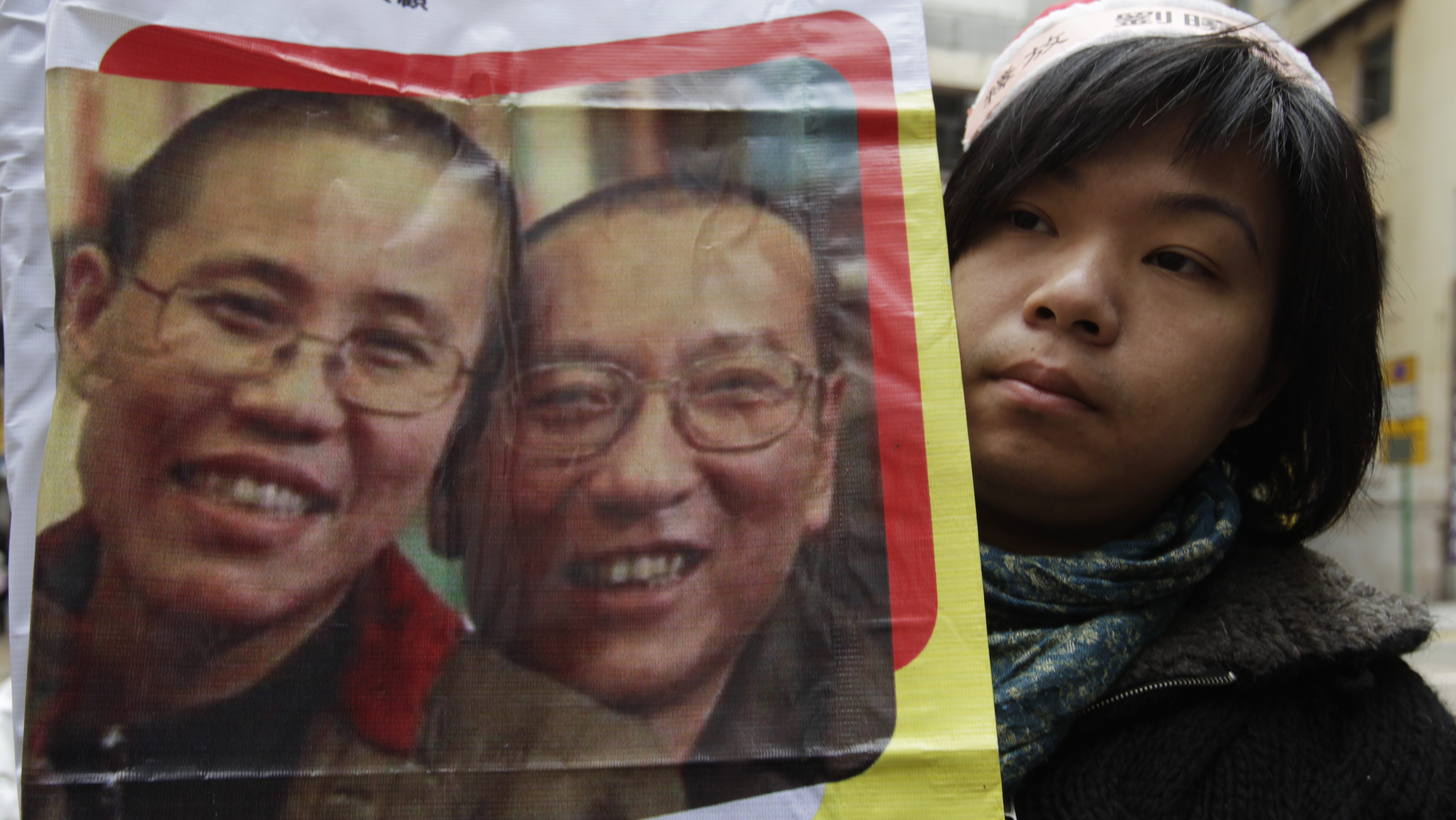 A pro-democracy protester holds a placard with picture of jailed Noble Peace Prize winner, Liu Xiaobo and his wife Liu Xia during a protest demanding China's government the release of Liu Xiaobo, outside the 'Chinese Liaison office in Hong Kong' in Hong Kong, China 25 December 2010. Lau was jailed for 11 years in 2009 on subversion charges.  EPA/YM YIK