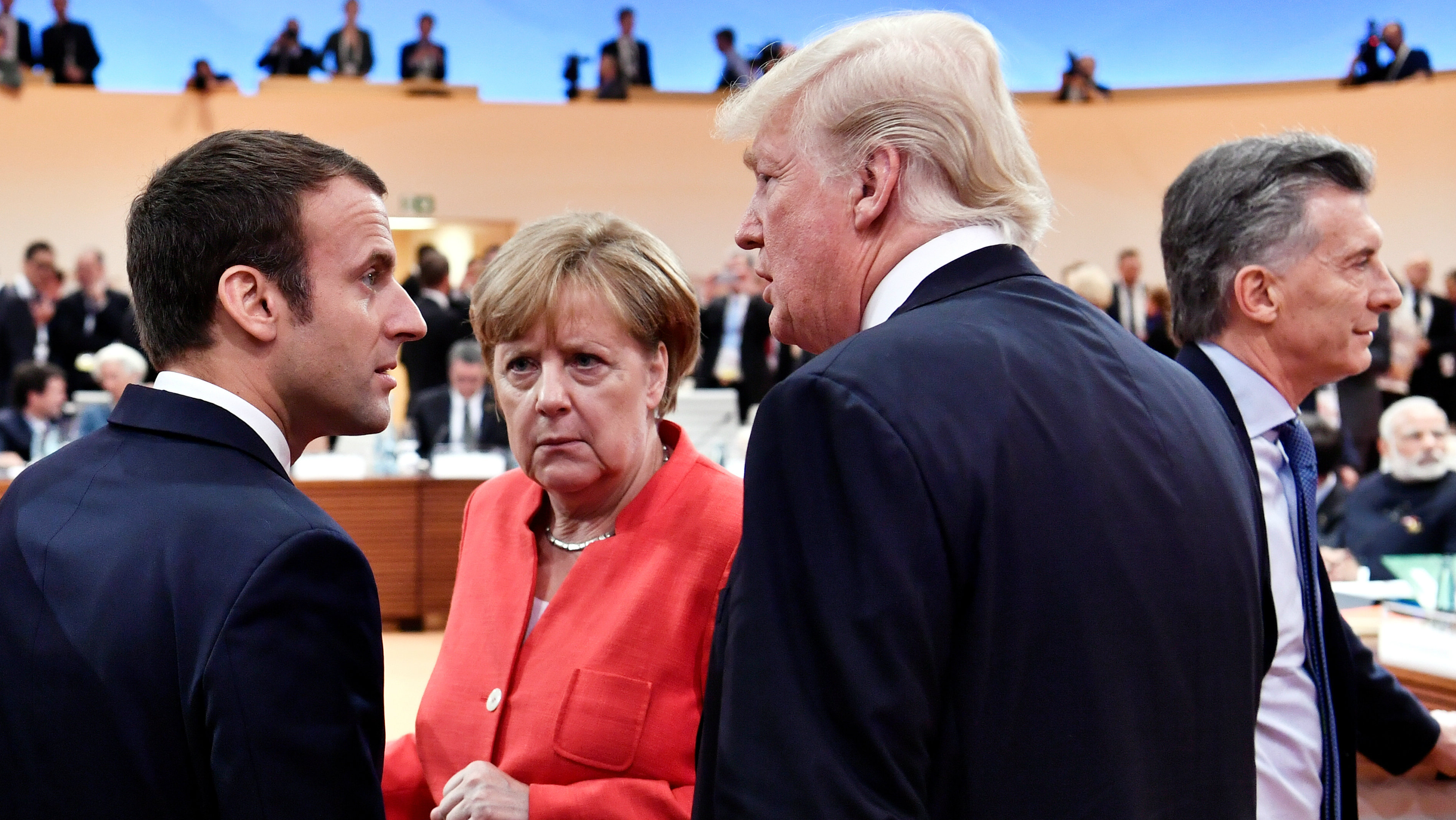 French President Emmanuel Macron, German Chancellor Angela Merkel and U.S. President Donald Trump confer s Argentinia's President Mauricio Macri walks past them at the start of the first working session of the G20 meeting in Hamburg, Germany, July 7, 2017.