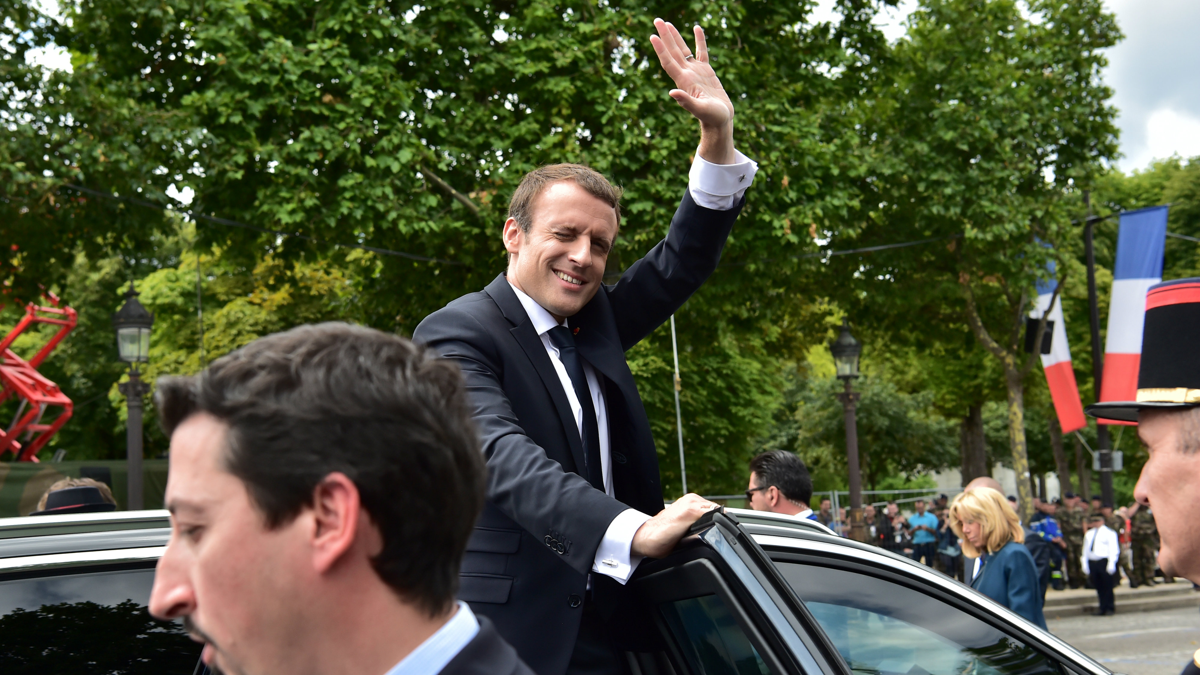French President Emmanuel Macron waves as he steps into a car after the traditional Bastille Day military parade on the Champs-Elysees avenue in Paris, France, July 14, 2017