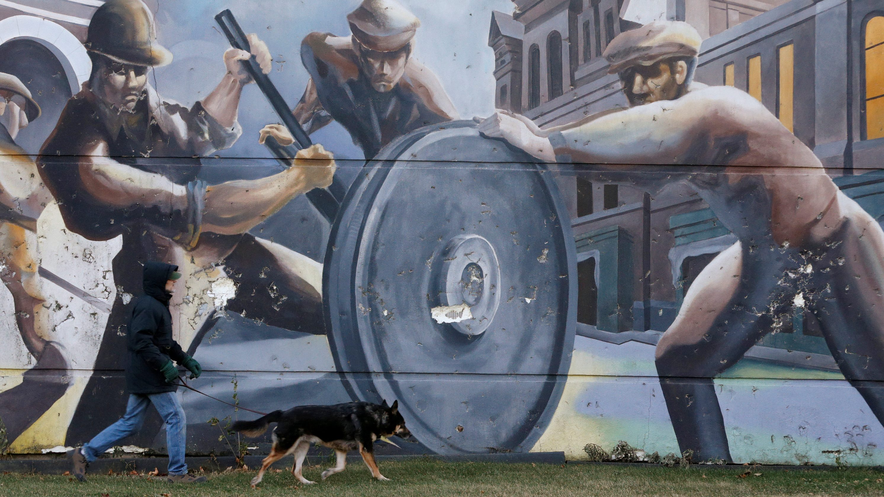 A man walks his dog past a mural depicting factory workers