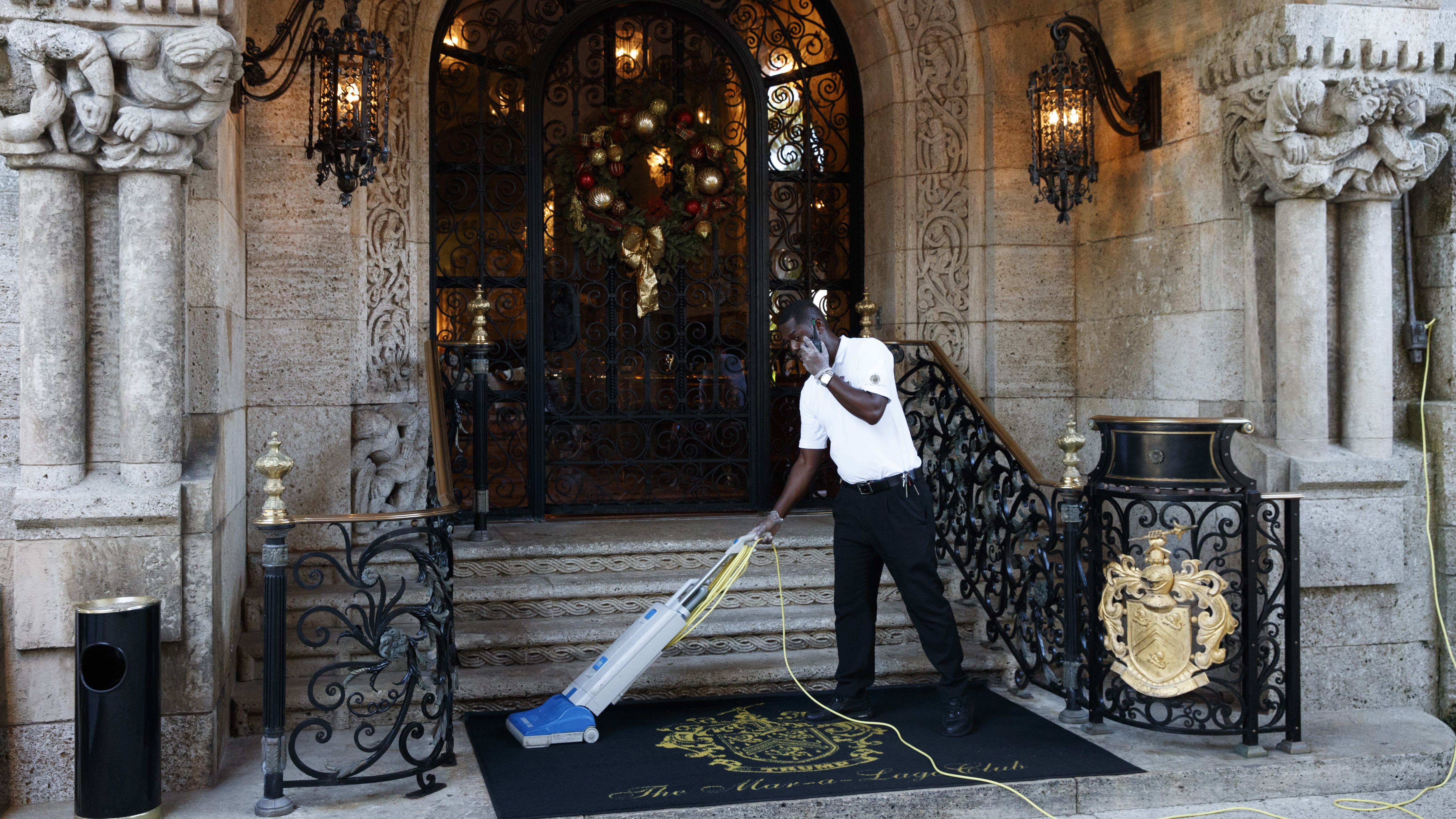 A worker vacuums the rug at the entrance to Mar-a-Lago