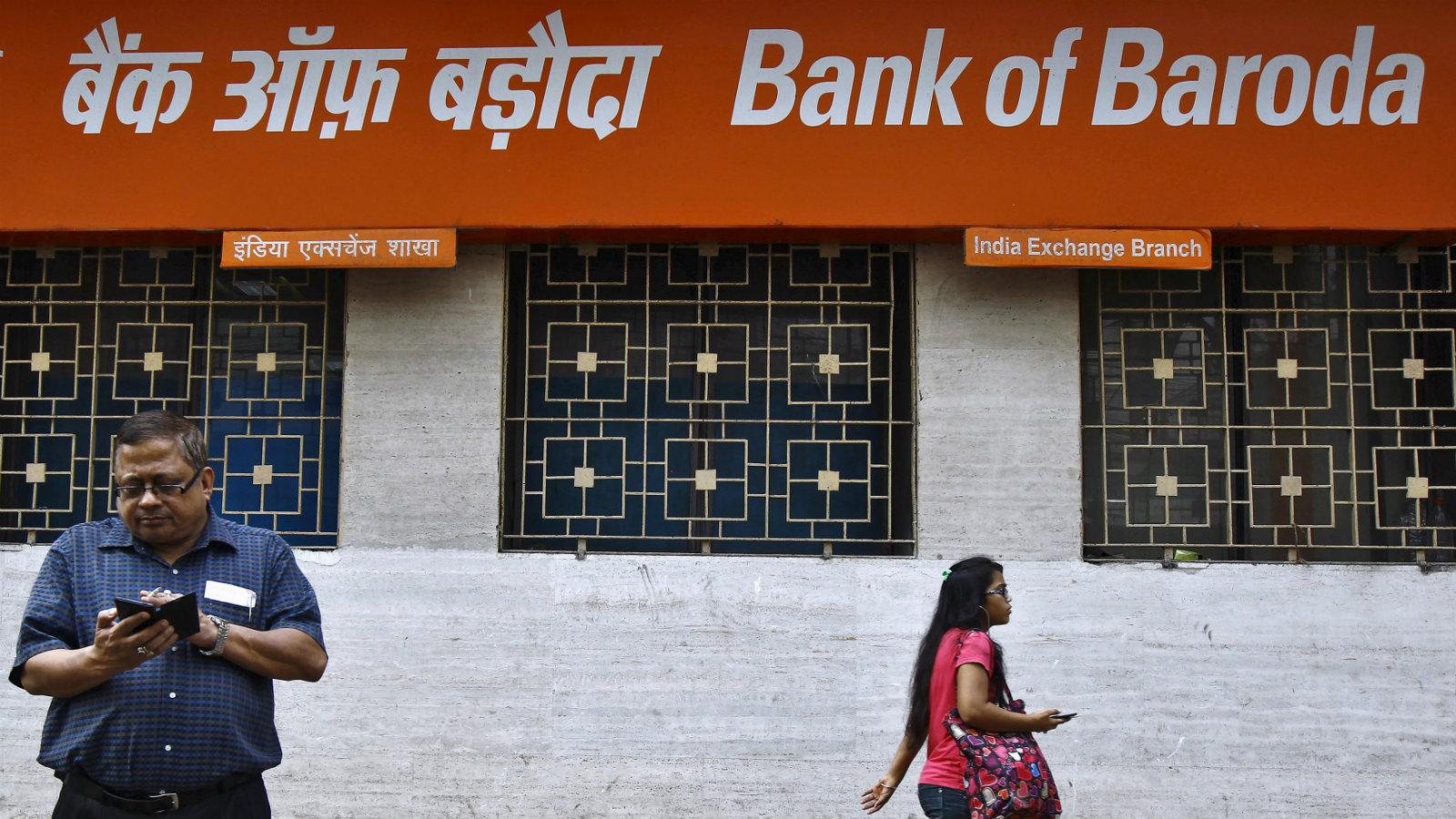 A man uses his mobile phone as a commuter walks past an advertisement of Bank of Baroda in Kolkata