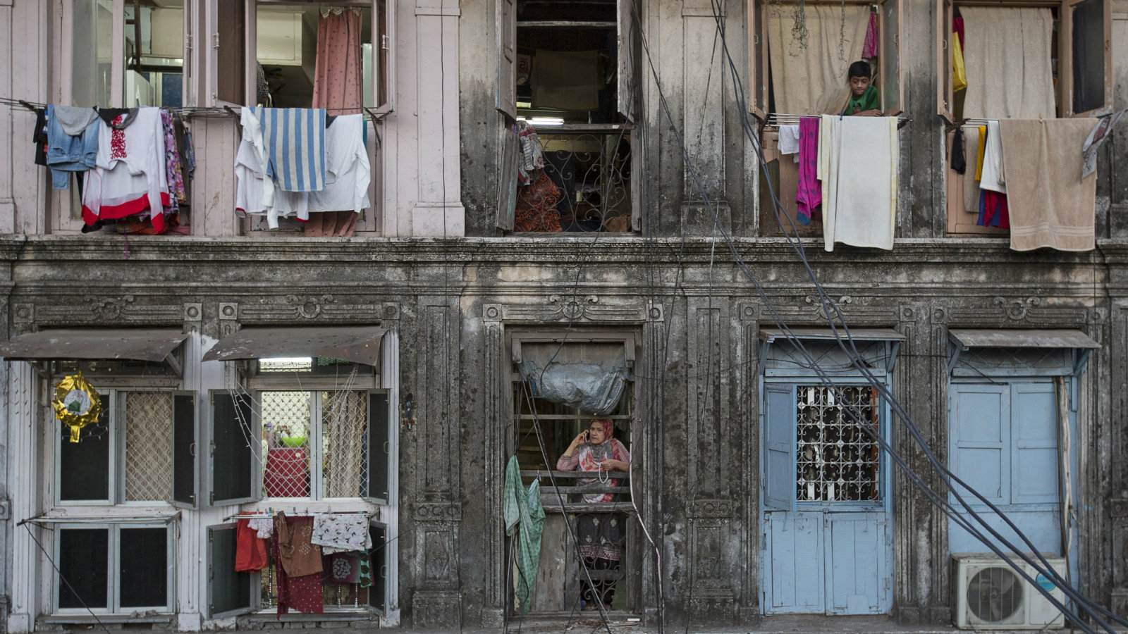 Residents look out of windows of an apartment in Mumbai March 15, 2015. The cost for buying a 200 square feet (18 square meters) one-bedroom apartment in this building is around 25,000 Indian rupees per square feet ($ 400) or 5,000,000 Indian rupees ($ 80,000). The rent for an apartment in the same building is around 12,000 Indian rupees ($ 190) per month.