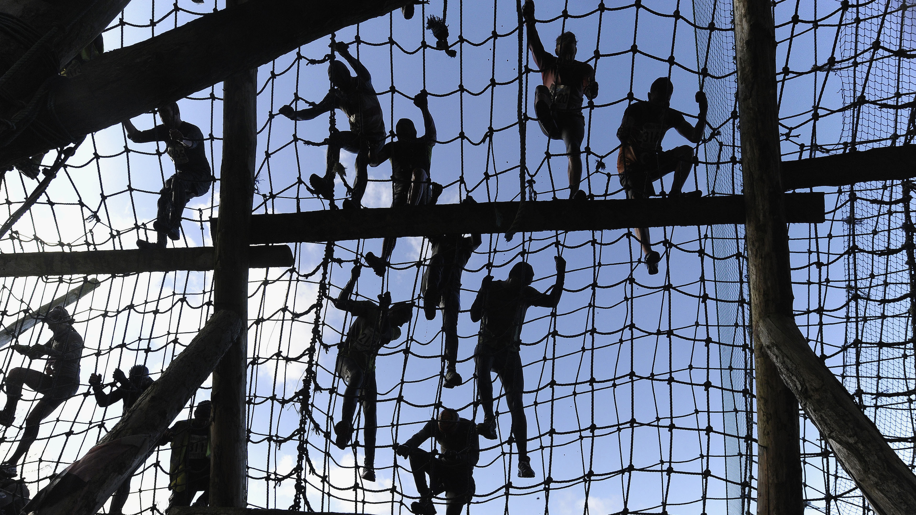 Competitors climb nets during the Tough Guy event in Perton, central England, January 27, 2013. The annual event to raise cash for charity challenges thousands of international competitors in a cross country run followed by an assault course consisting of obstacles including water, fire and tunnels.