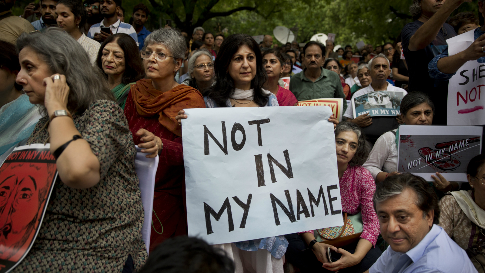 """An Indian woman holds placard and listens to a speaker during a protest against a spate of violent attacks across the country targetting the country's Muslim minority, in New Delhi, India, Wednesday, June 28, 2017. Carrying placards that said """"not in my name,"""" the protestors on Wednesday decried the silence of India's Hindu rightwing government in the face of the public lynchings and violent attacks on at least a dozen Muslim men and boys since it came to power in 2014."""