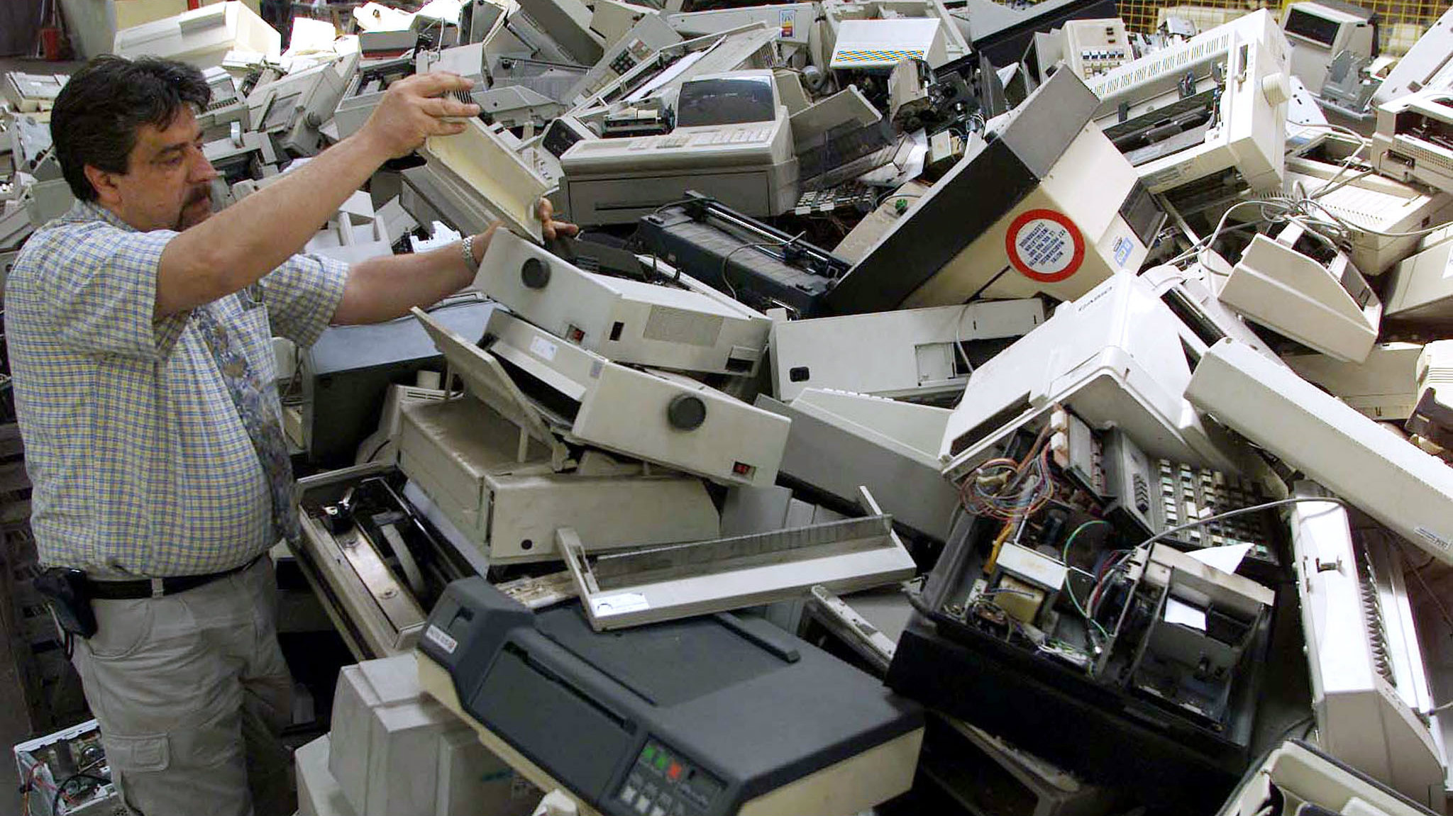 Patrick Maranon sorts through computer printers and fax machines at his Ecomicro recycling company in Bordeaux, June 11, 2001. Ecomicro claims to be the only company in France which yearly separates some 1500 tonnes of obsolete or unuseable computers into separate components for recycling.