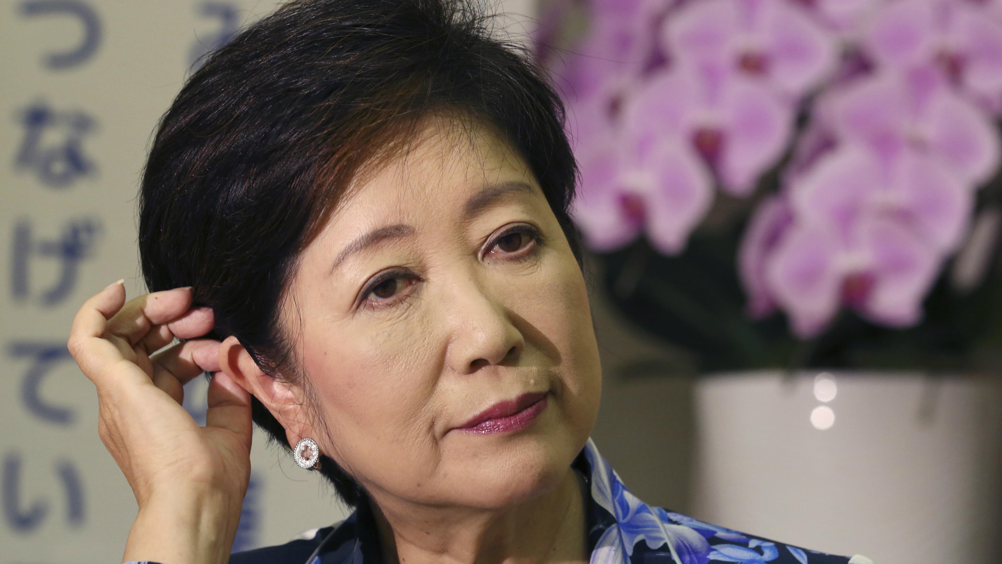 Tokyo Governor Yuriko Koike adjusts her hair during an interview