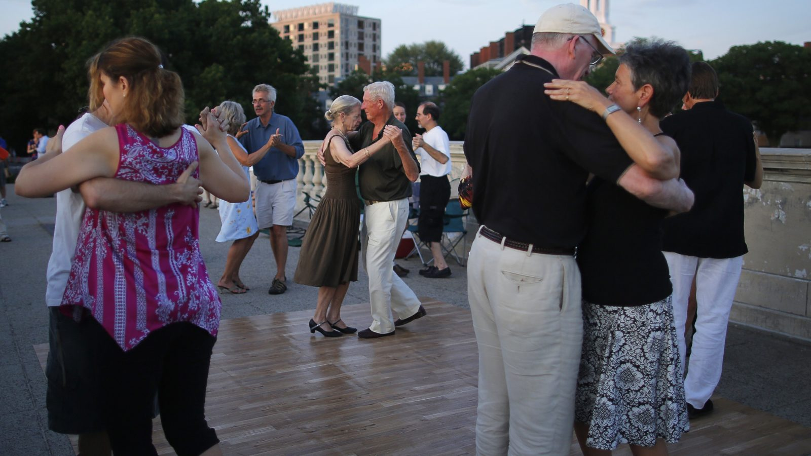 Couples, including Ellen and Larry Walsh (C), dance during one of the Tango Society of Boston's Tango by Moonlight evenings on the Weeks Footbridge over the Charles River in Cambridge, Massachusetts July 6, 2013.  This is the society's 17th Tango by Moonlight season.    REUTERS/Brian Snyder  (UNITED STATES - Tags: SOCIETY) - RTX11FAG