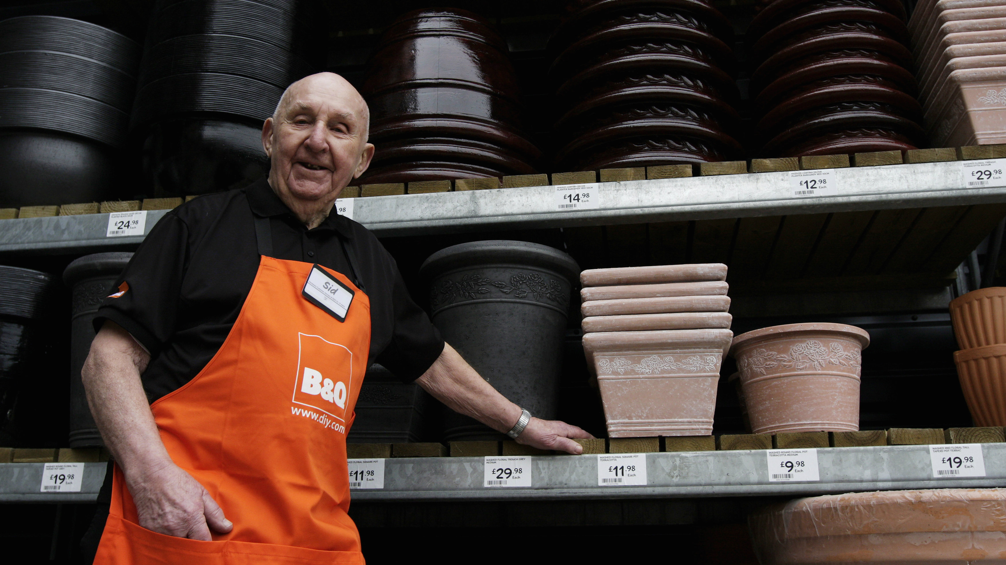 Employee Sydney Prior, 95, poses for a portrait at the B&Q store in the southwest London suburb of New Malden, March 24, 2010. The participation of older workers has increased in recent years, particularly in part-time jobs for men like Prior, whose employer, retail chain B&Q, has for decades made a public point of its enthusiasm for older staff.