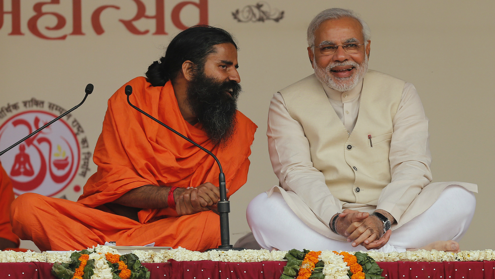 Hindu nationalist Narendra Modi, prime ministerial candidate for India's main opposition Bharatiya Janata Party (BJP) shares a moment with Indian yoga guru Baba Ramdev (L) during a Yoga Mahotsav or festival, in New Delhi March 23, 2014. The mega 'Yoga Mahotsav' on Sunday is being observed simultaneously at various places across the country, local media reported.